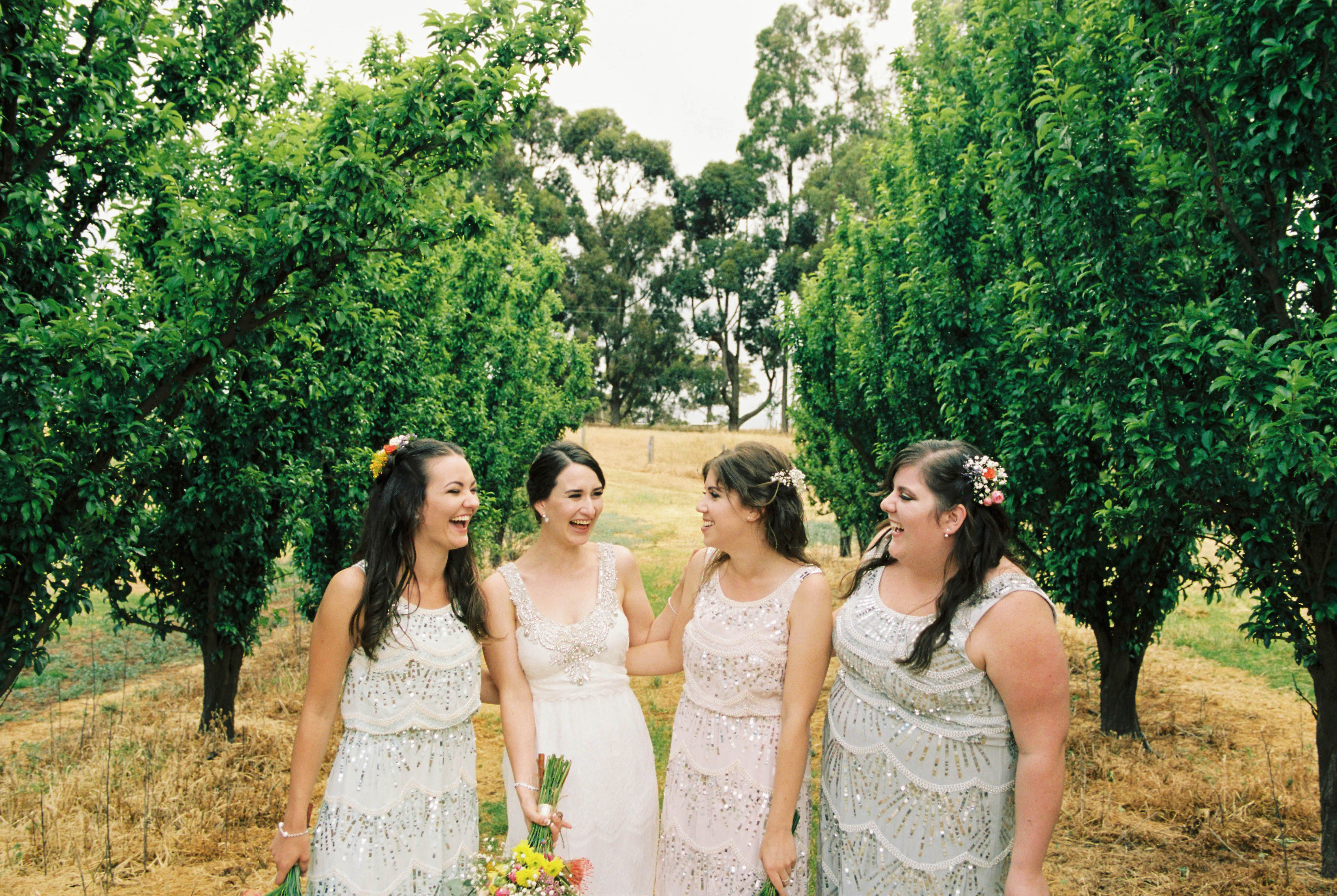 Authentic South West Wedding Photography of the bride and her bridesmaids laughing together