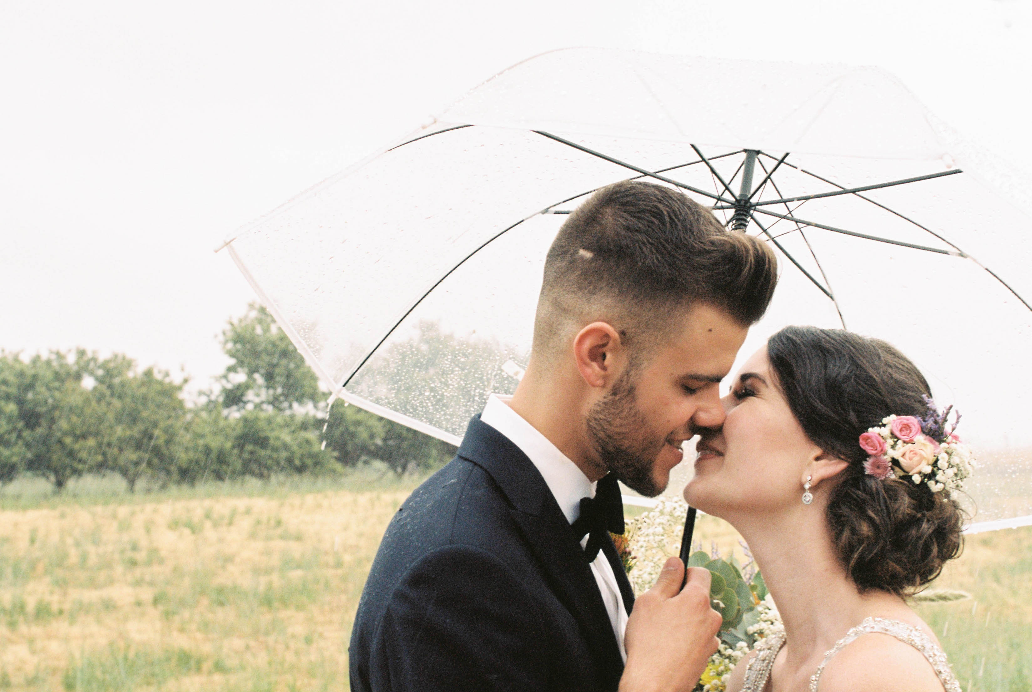 Candid wedding photography of the bride & groom sharing a moment under a clear plastic umbrella