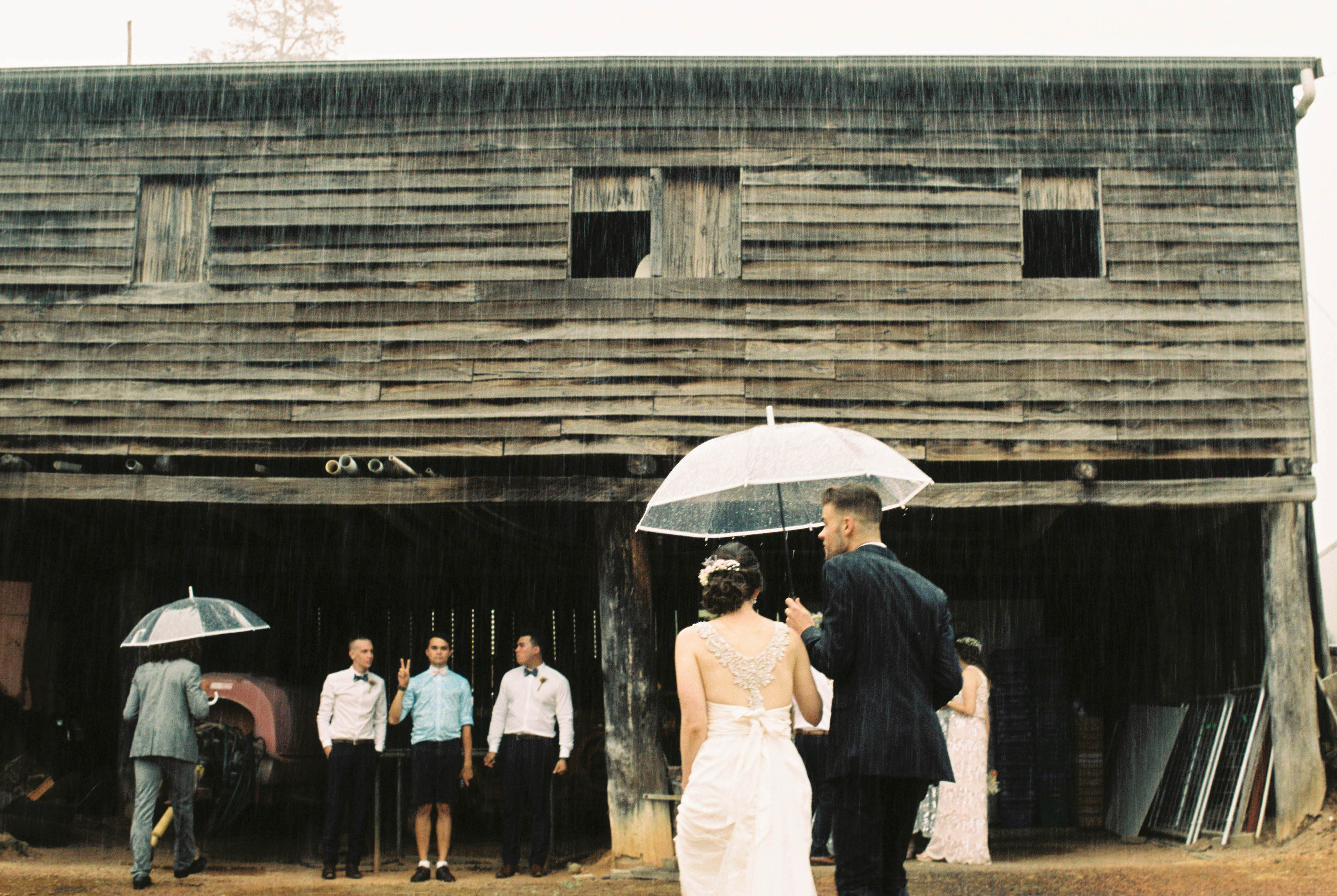 A photo of the bridal party waiting under an old farm shed while the bride & groom walk back to them