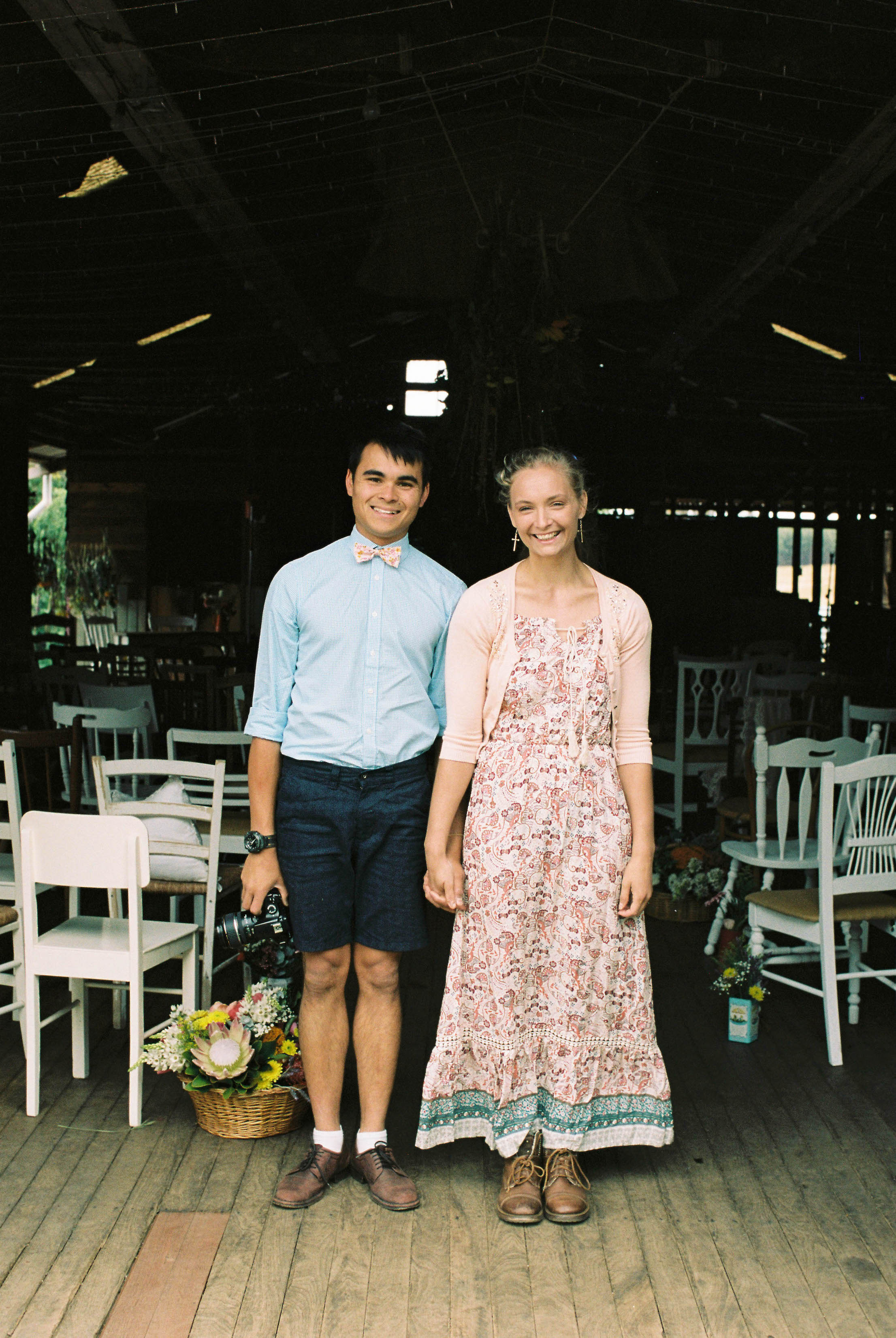 A photo of a couple in front of a ceremony in a shearing shed in Bridgetown before a wedding