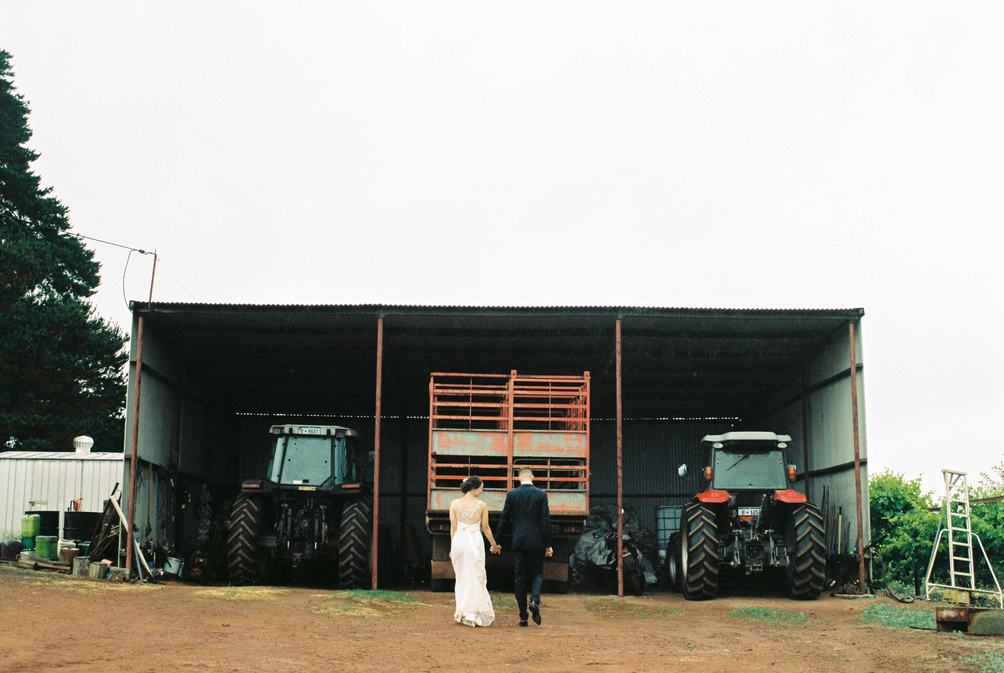 Wedding portraits of the bride & groom standing in front of an old farm shed filled with trucks and tractors