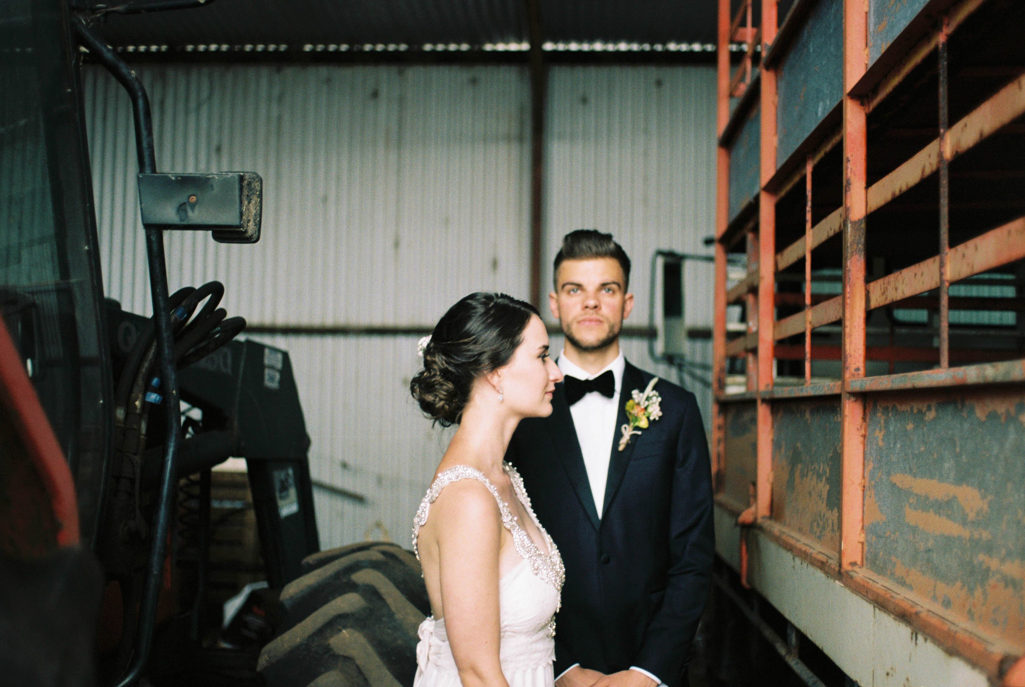 A posed portrait of the groom & bride standing in an old farm shed