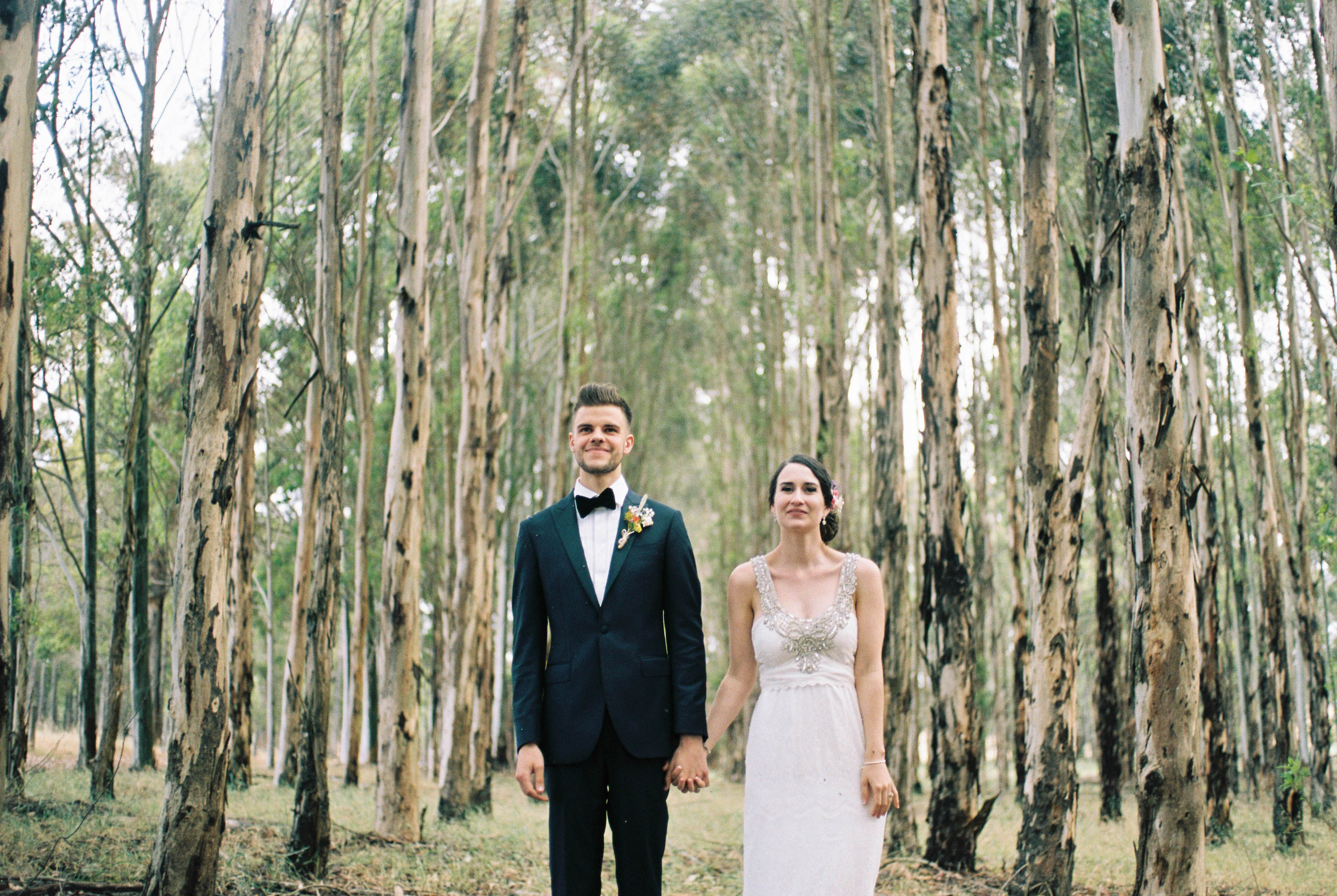 Natural wedding portraits of the bride and groom standing side by side in a blue gum plantation