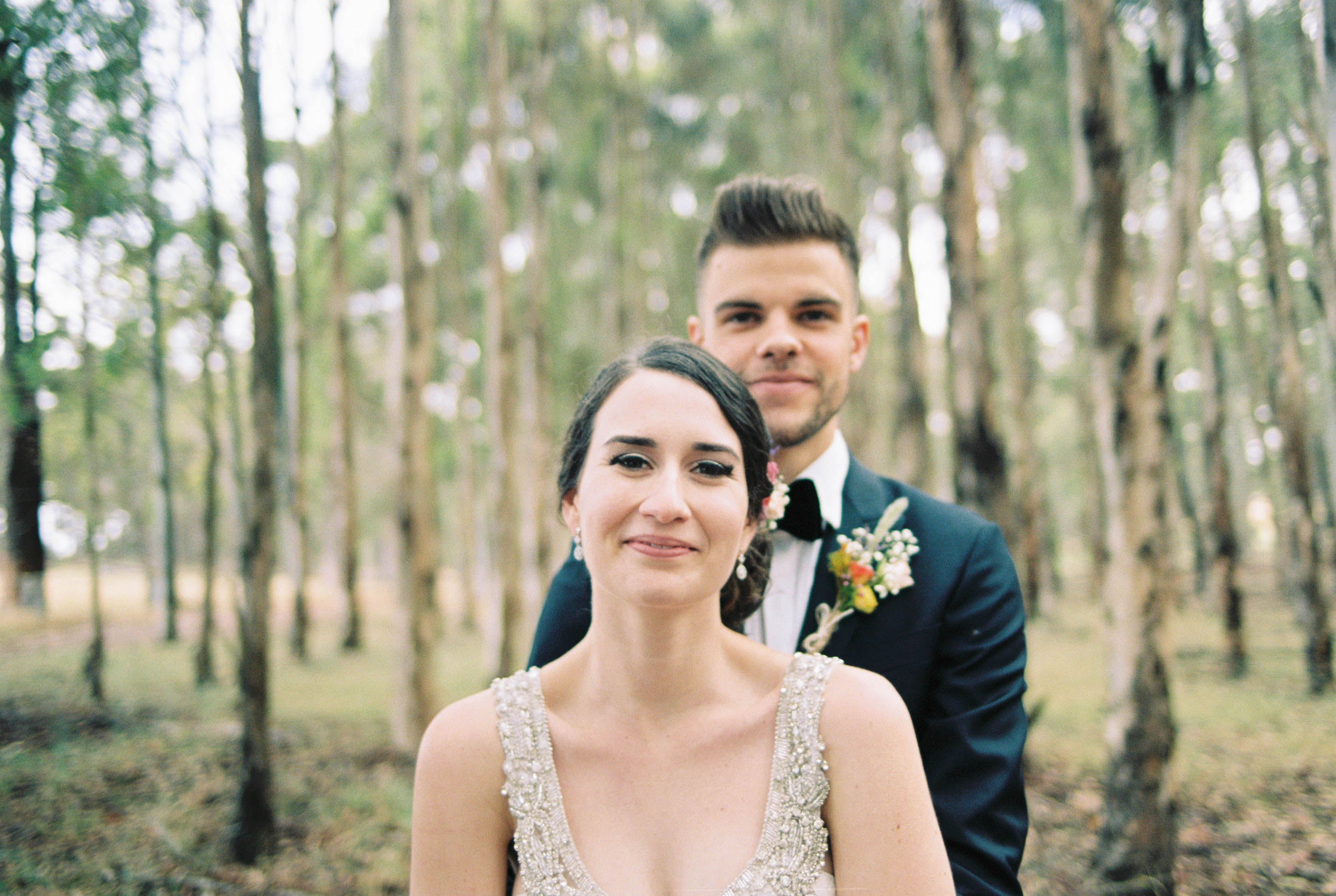 A portrait of the bride and groom cuddling in a blue gum plantation
