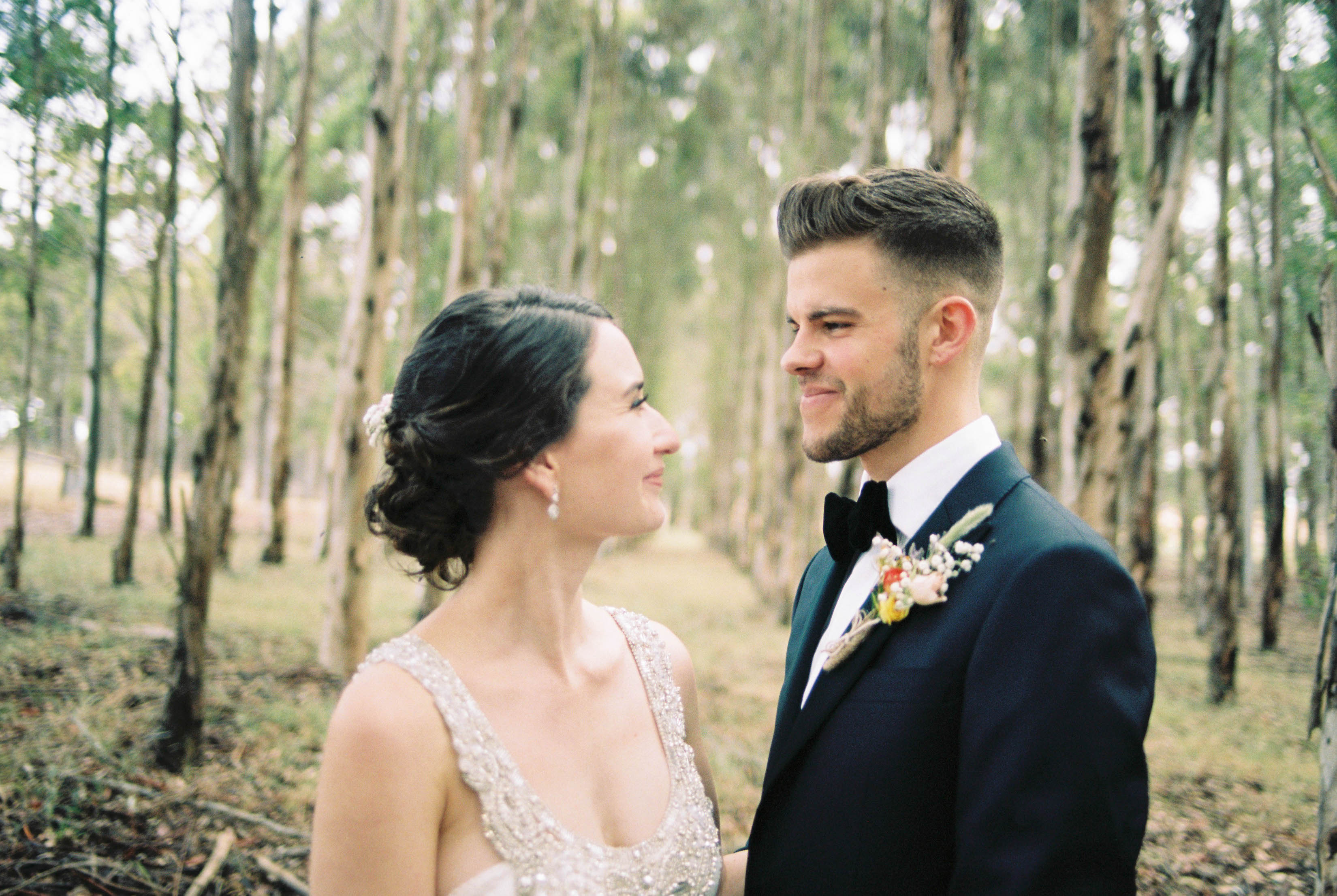 Authentic wedding portraits of the bride and groom smiling at each other in a blue gum plantation