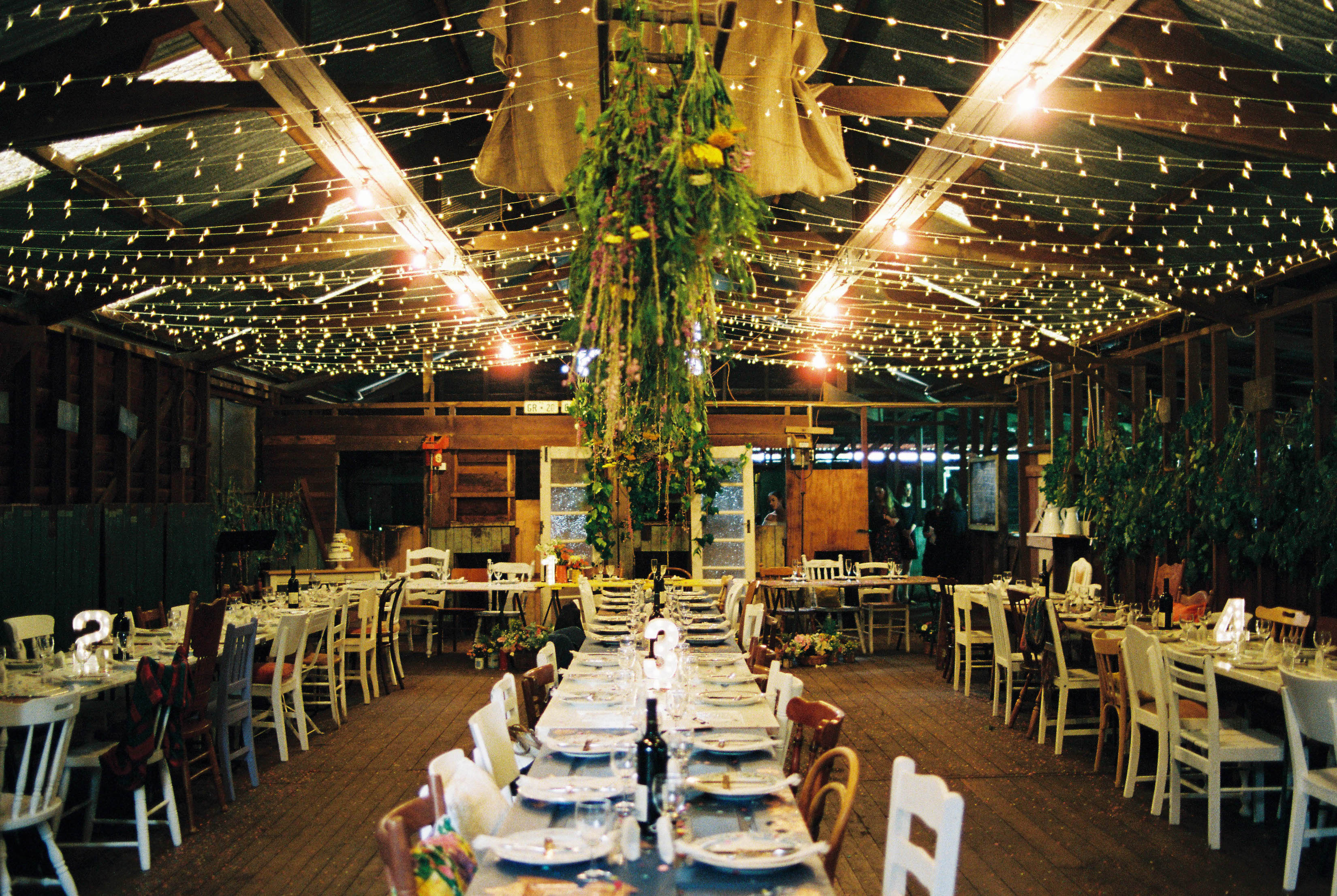 A wide shot of a shearing shed wedding reception, featuring fairy lights and mismatched boho styling taken by an Australian Italian Destination Wedding Photographer