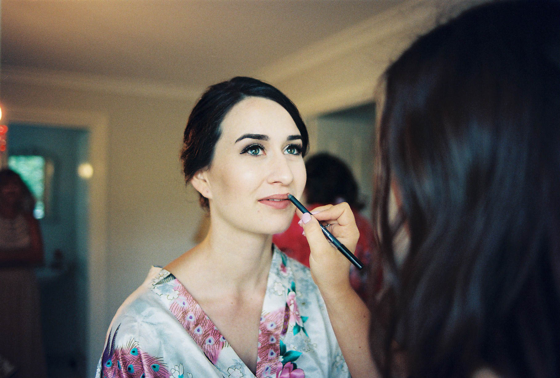A photo of the bride having her lipstick applied before her wedding in Balingup, Western Australia