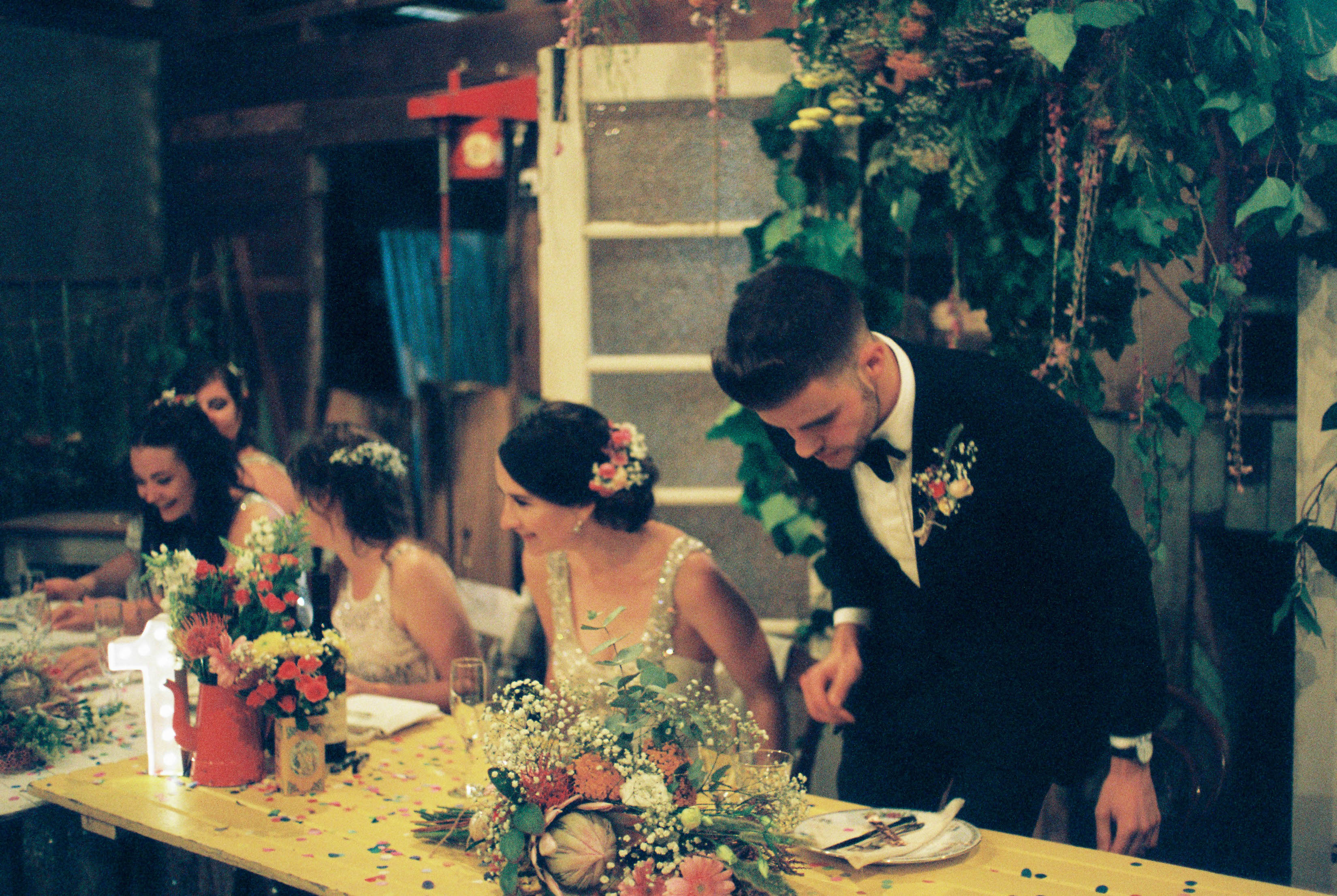An authentic analogue photography of the bride & groom sitting down at their shearing shed reception