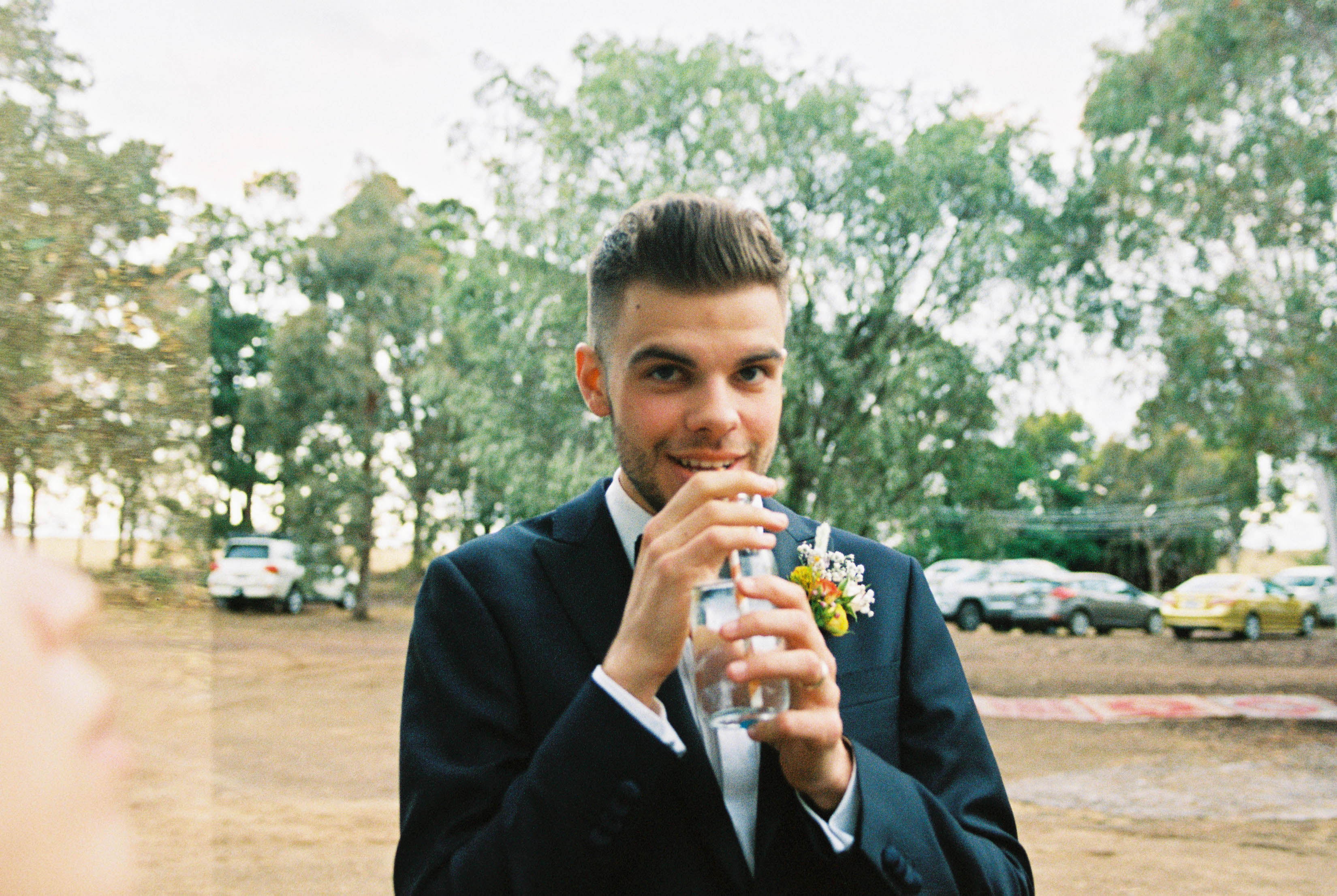 A photo of the groom smiling while he takes a sip of his drink taken by Bridgetown Wedding Photographer