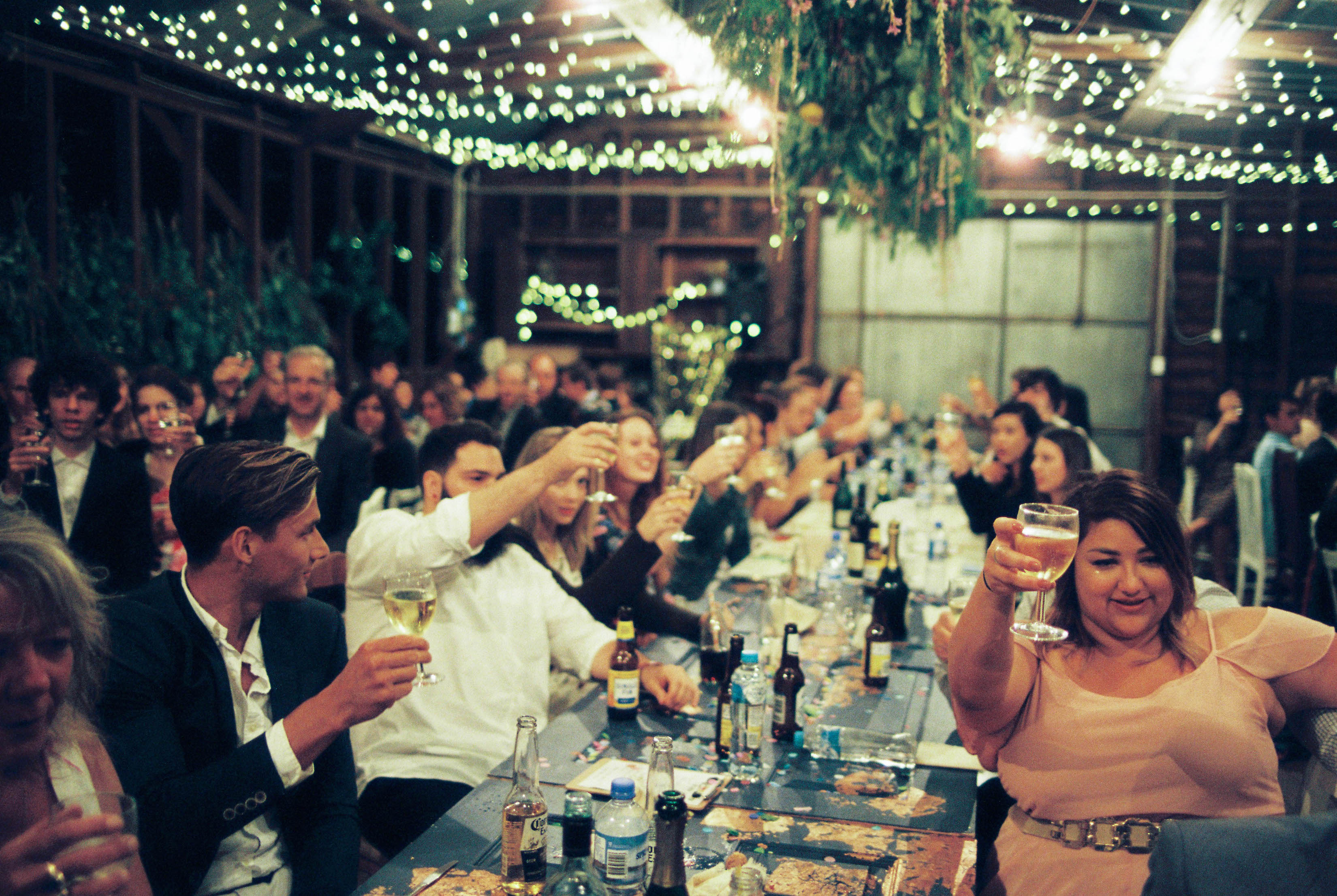 An analogue photo of guests at a long table wedding reception while they 'cheers!'