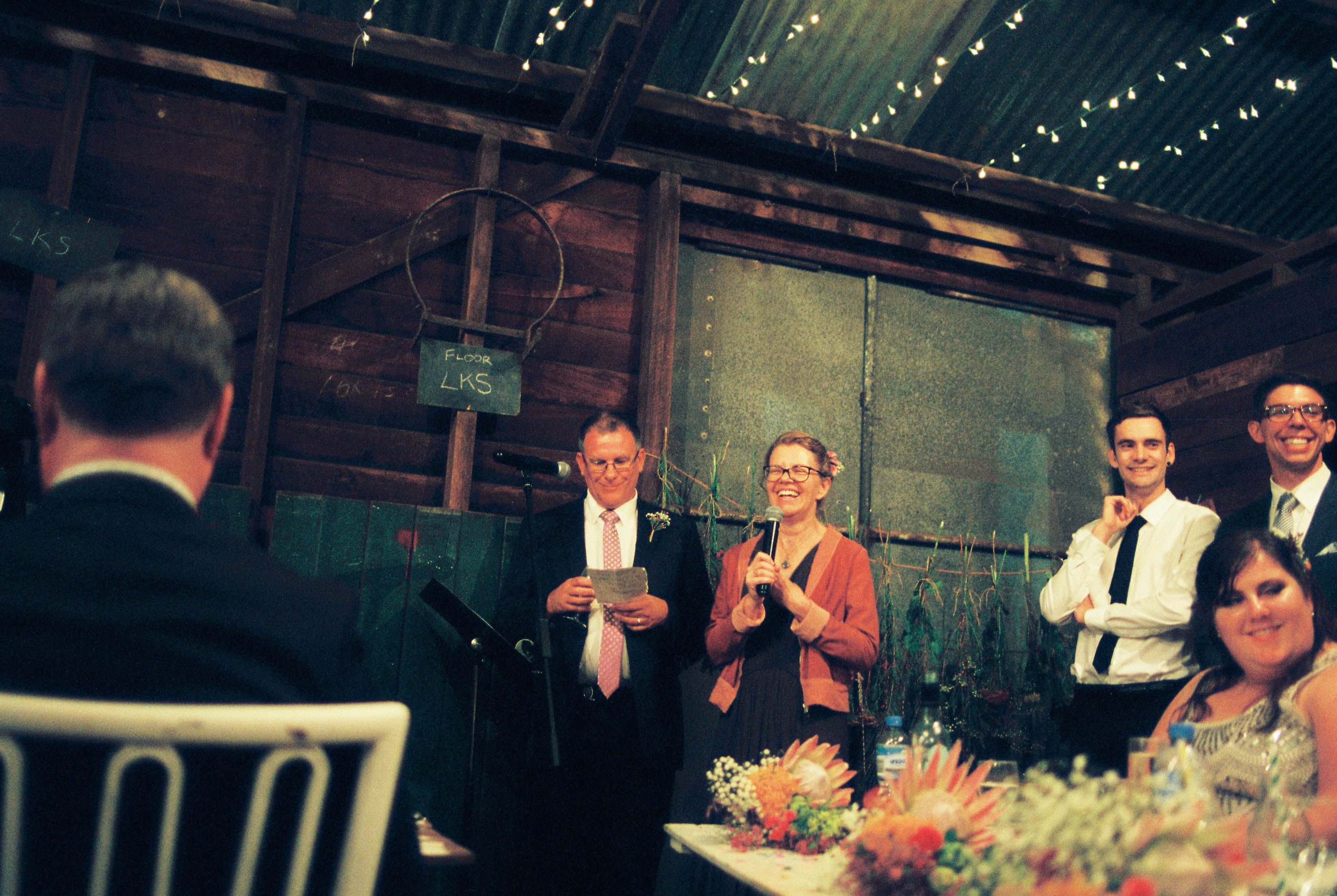Honest Wedding Photography of the Groom's Parents giving their speech