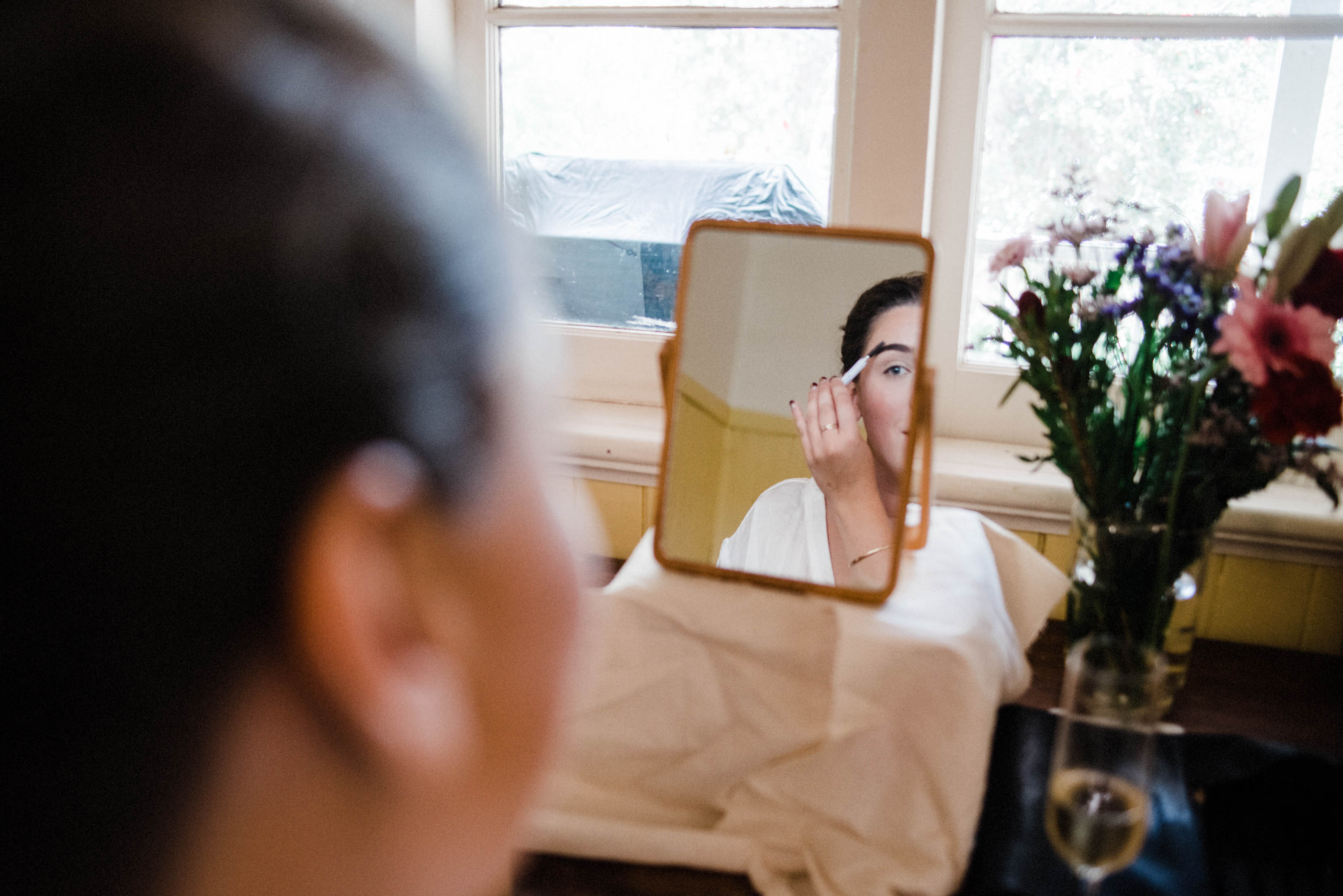 Documentary wedding photography of a bride doing her makeup reflected in a small mirror.