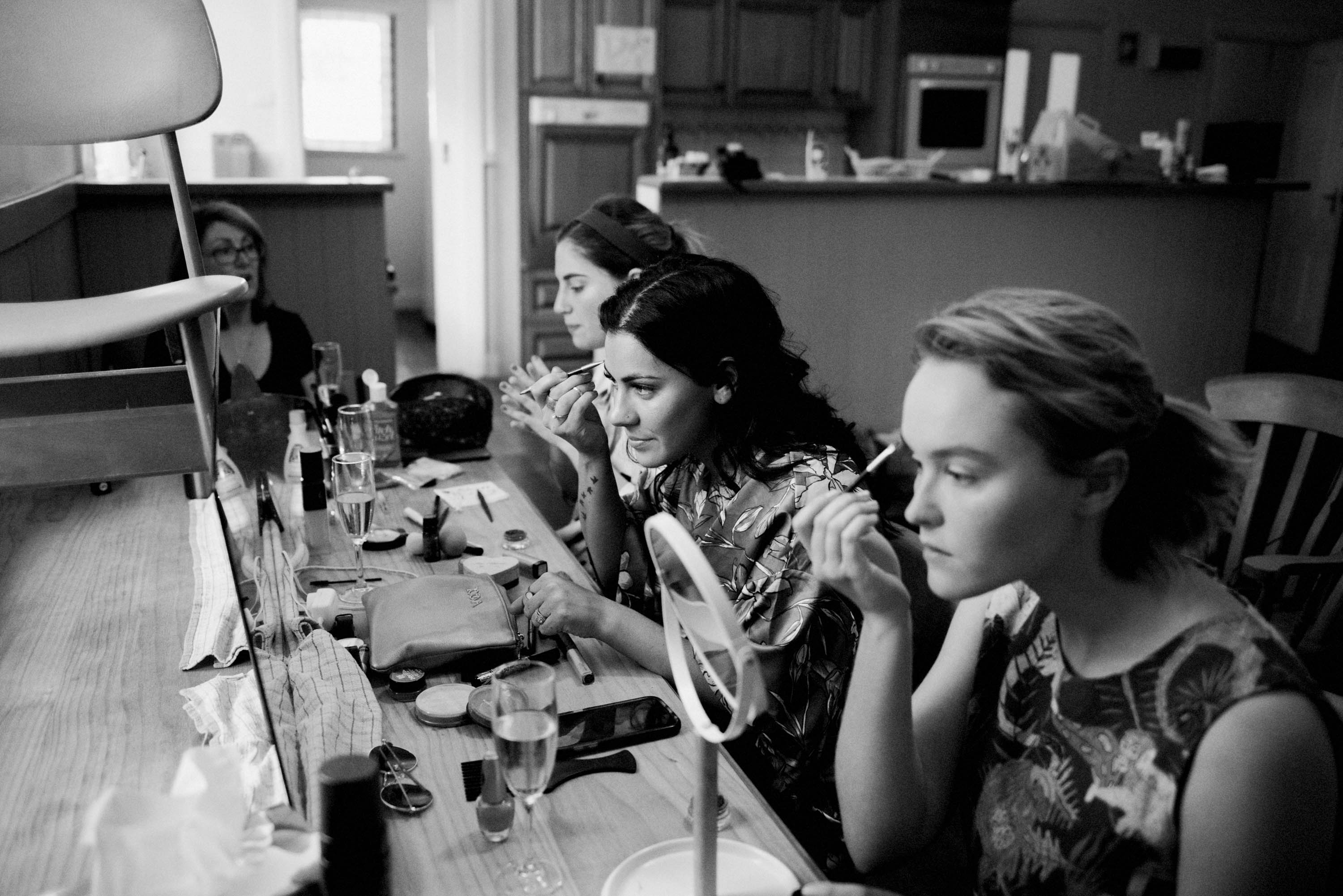A black and white photo of bridesmaids doing their makeup at a long table.