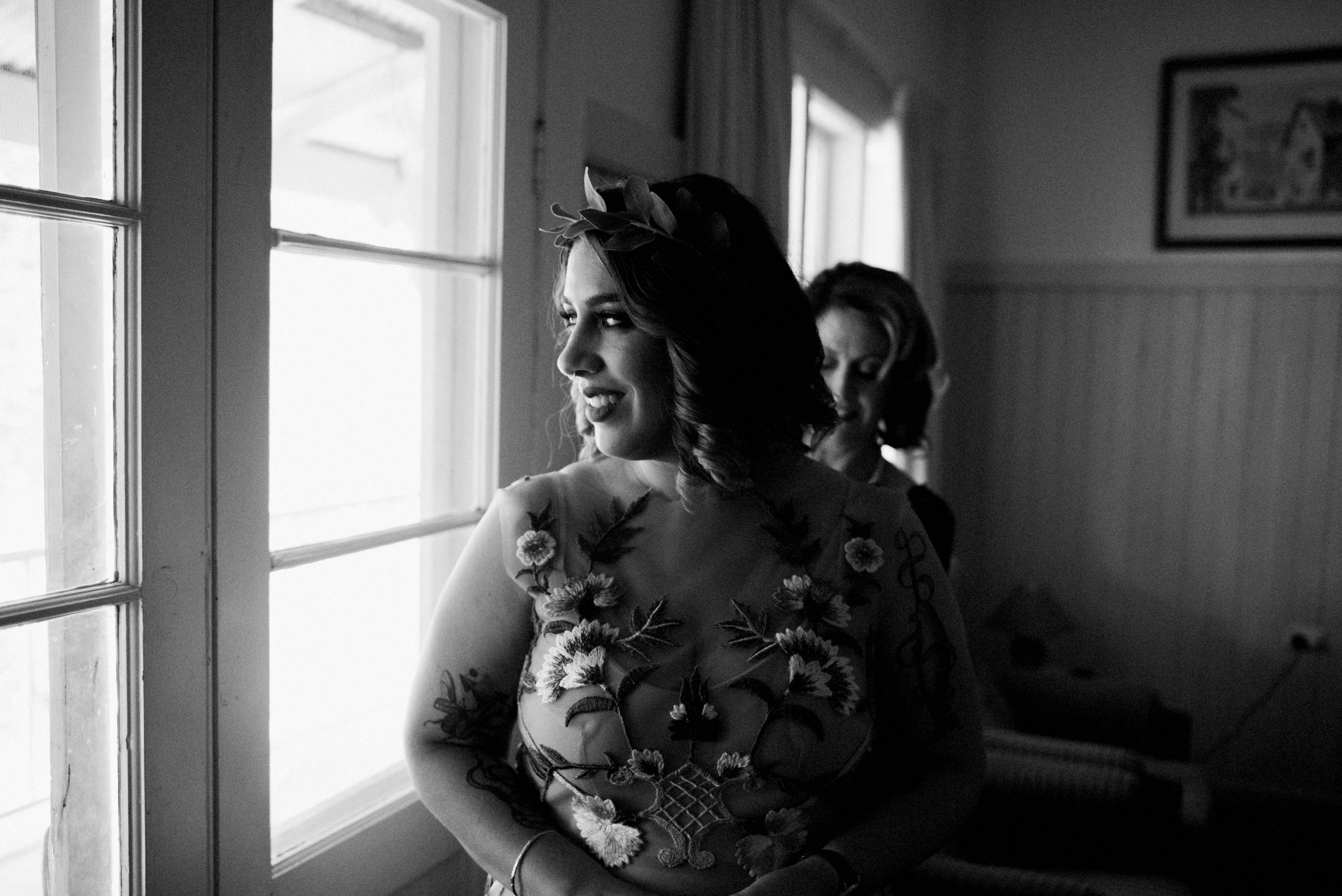A black & white wedding photo of the bride's mum helping her with her dress.