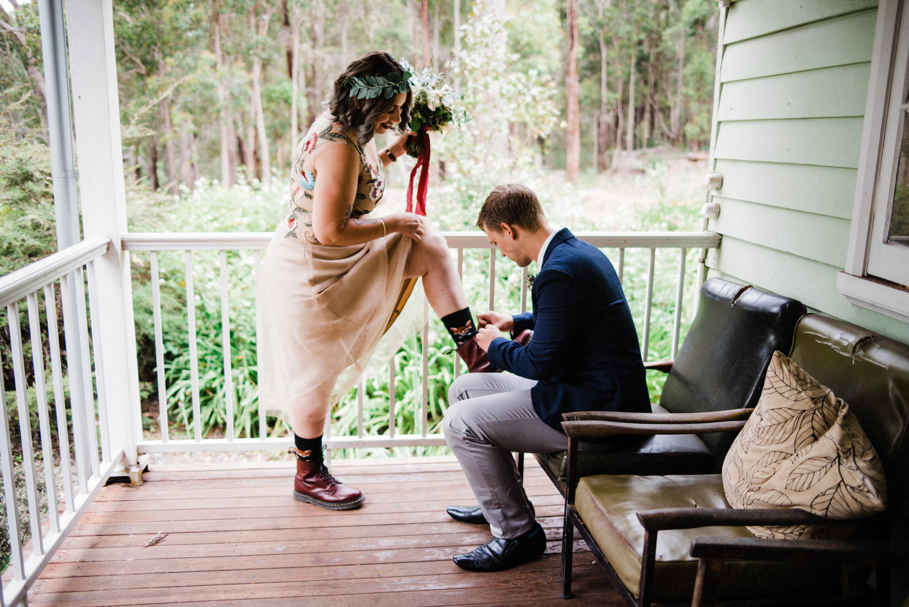 The brides-man helps the Bride with her Dr Marten shoes the morning of her wedding.