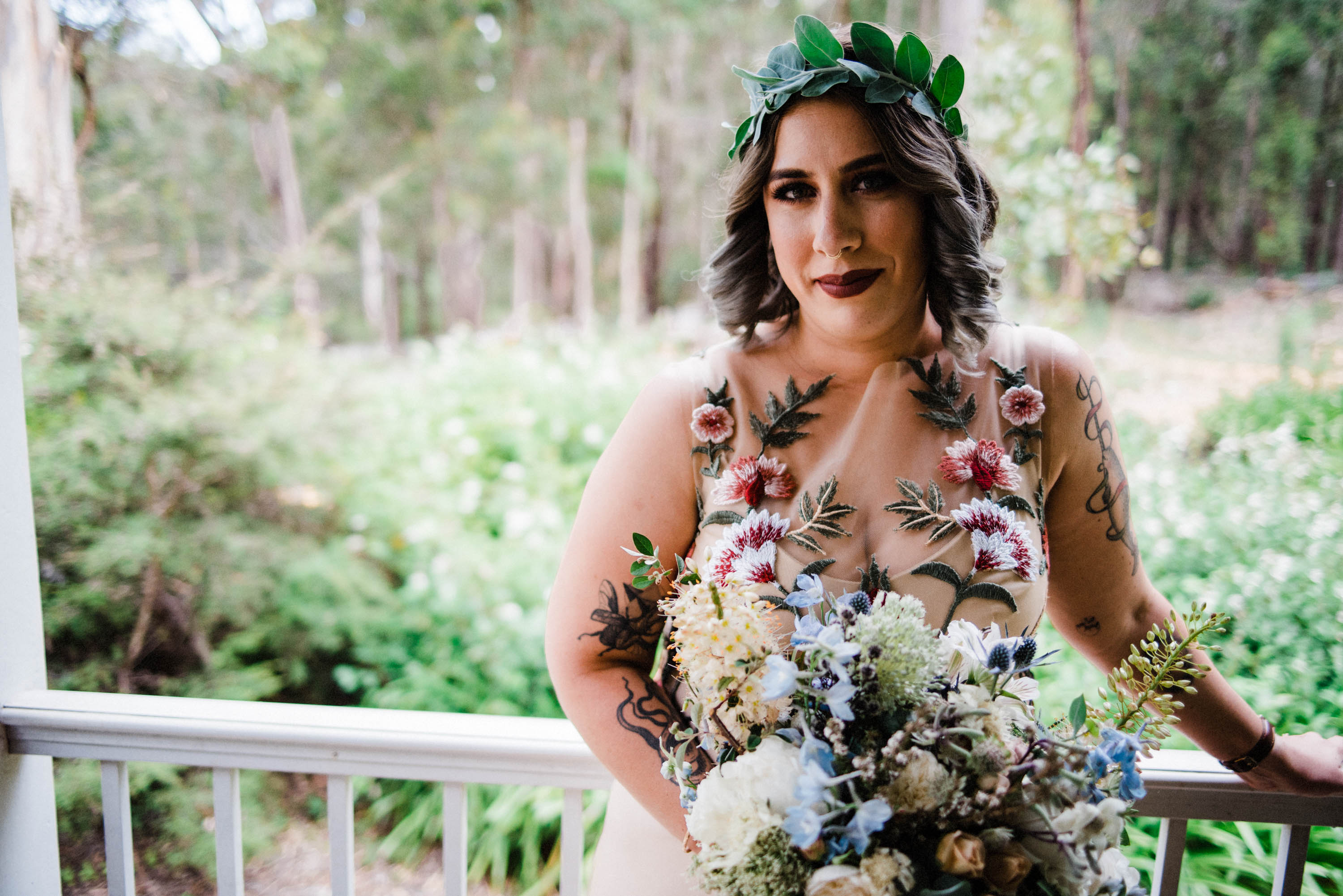 A portrait of the bride on the morning of her wedding, wearing a custom Harriette Gordon dress, foraged eucalyptus in her hair and a Covet Collect bridal bouquet.