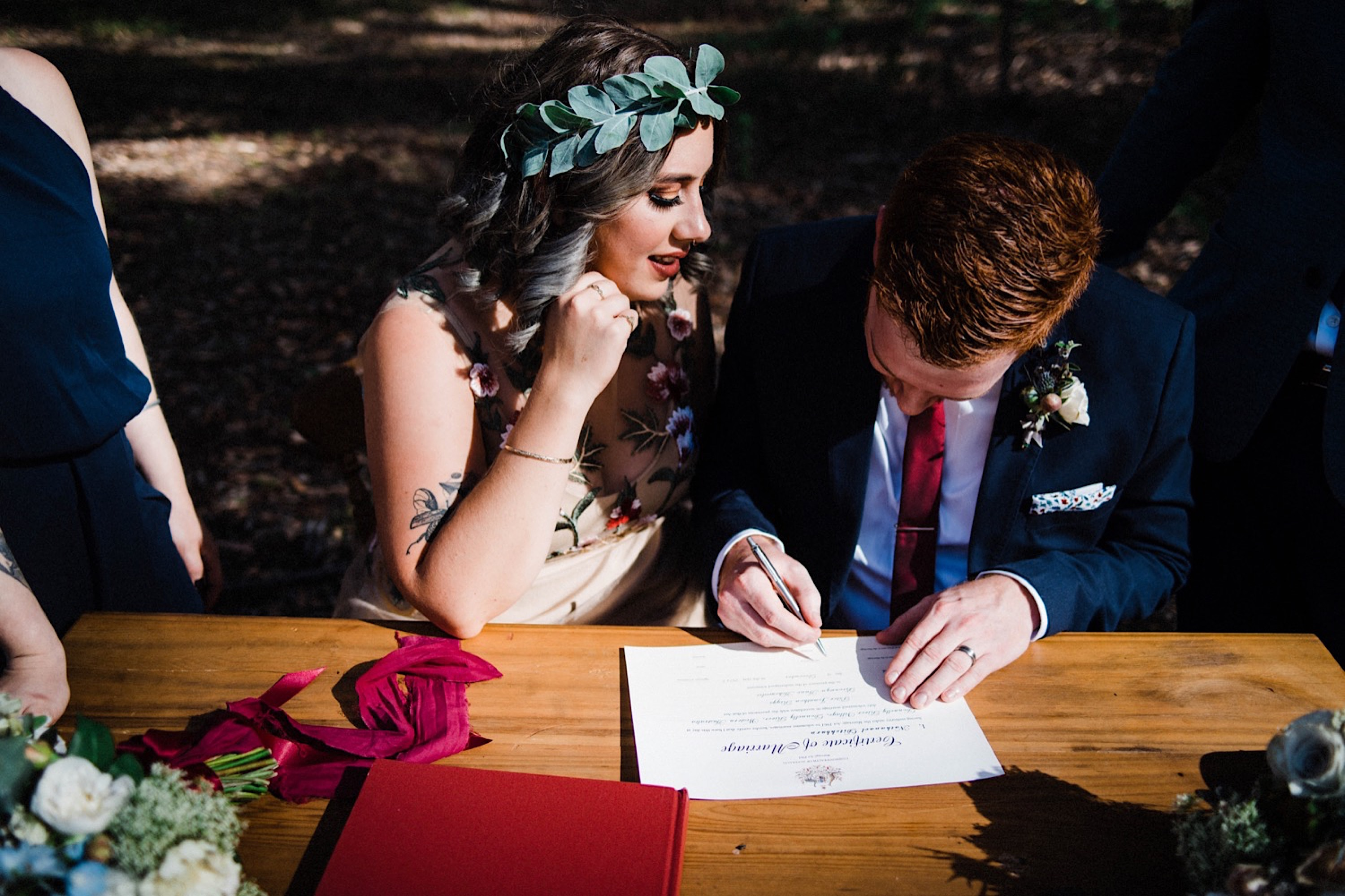Authentic wedding photography of the bride & groom singing their Australian wedding certificate.