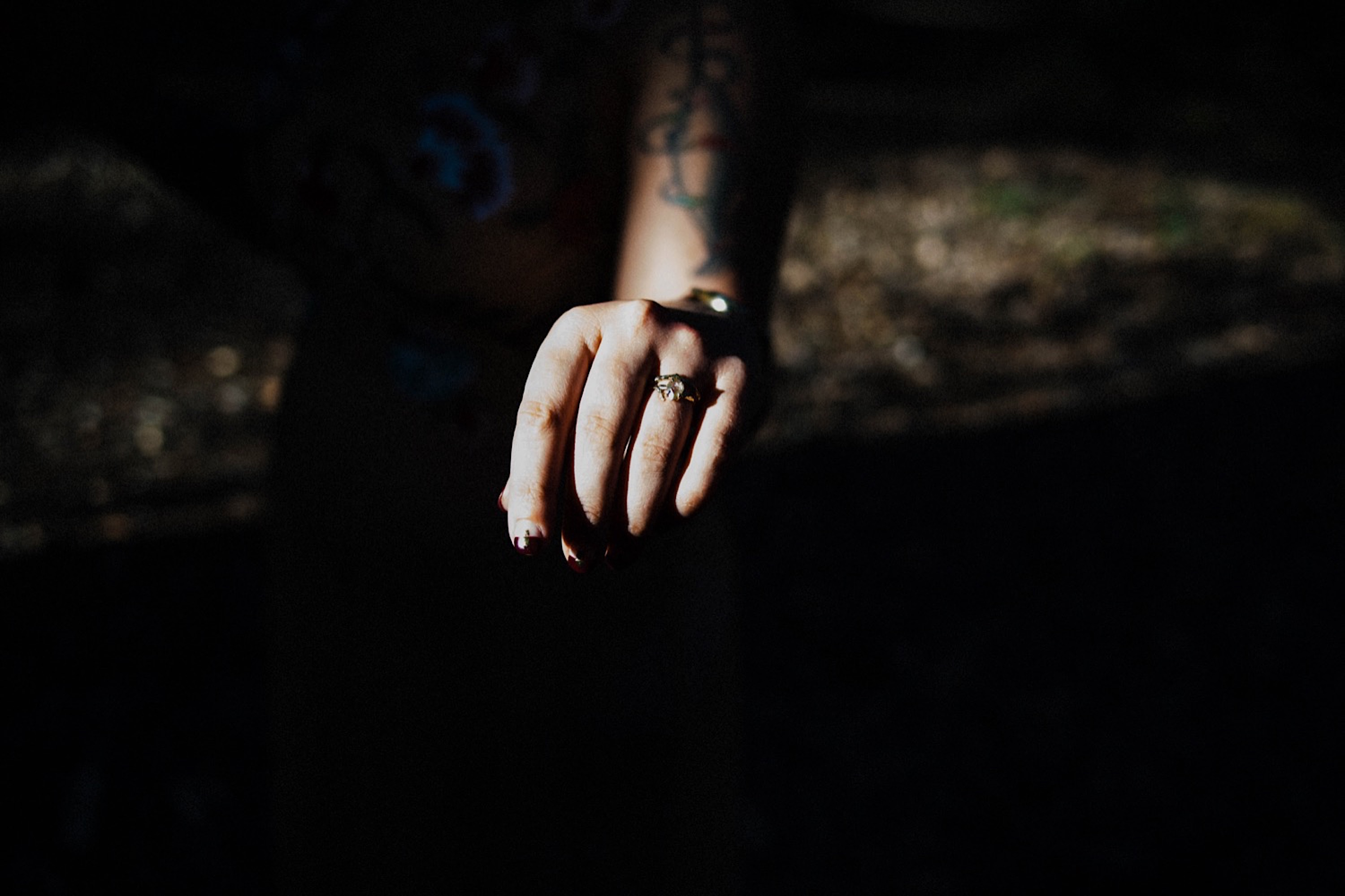 A dark & moody wedding photo of the bride's ethical engagement and wedding rings.