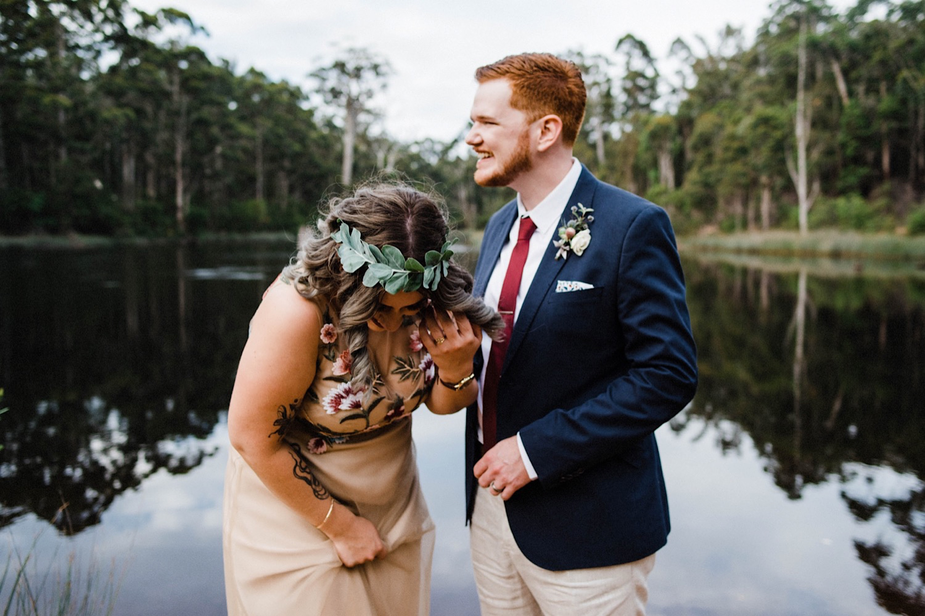 Authentic Wedding Photography of the Bride & Groom laughing at the Donnelly River Village Dam.