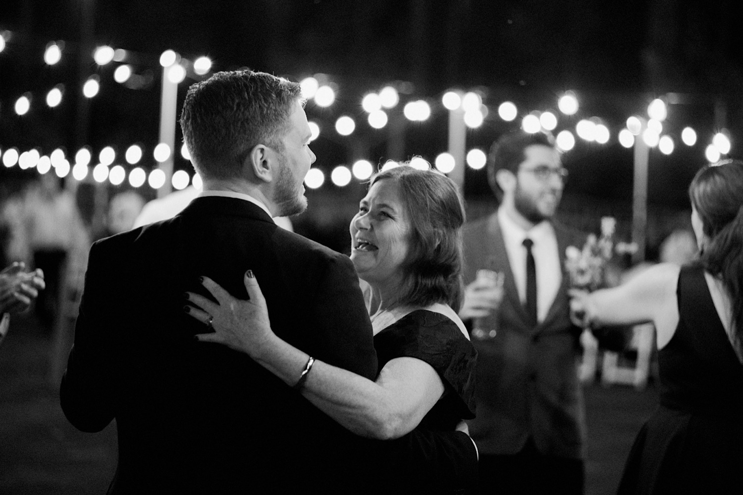 A black & white candid wedding portrait of the Groom & his Mum dancing together.