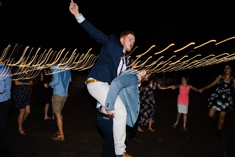 A dancefloor wedding photo of the best man giving the groom a piggyback.