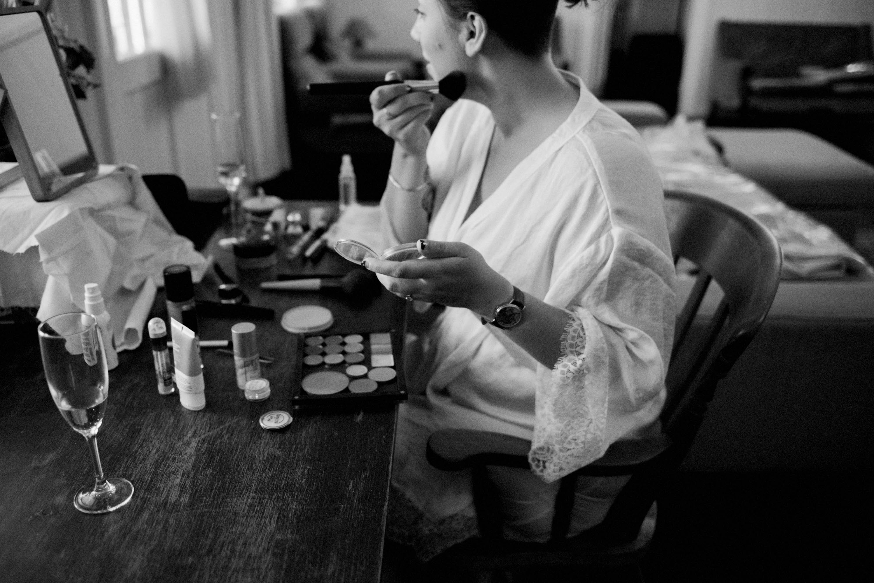 A black & white photo of the bride doing her makeup.