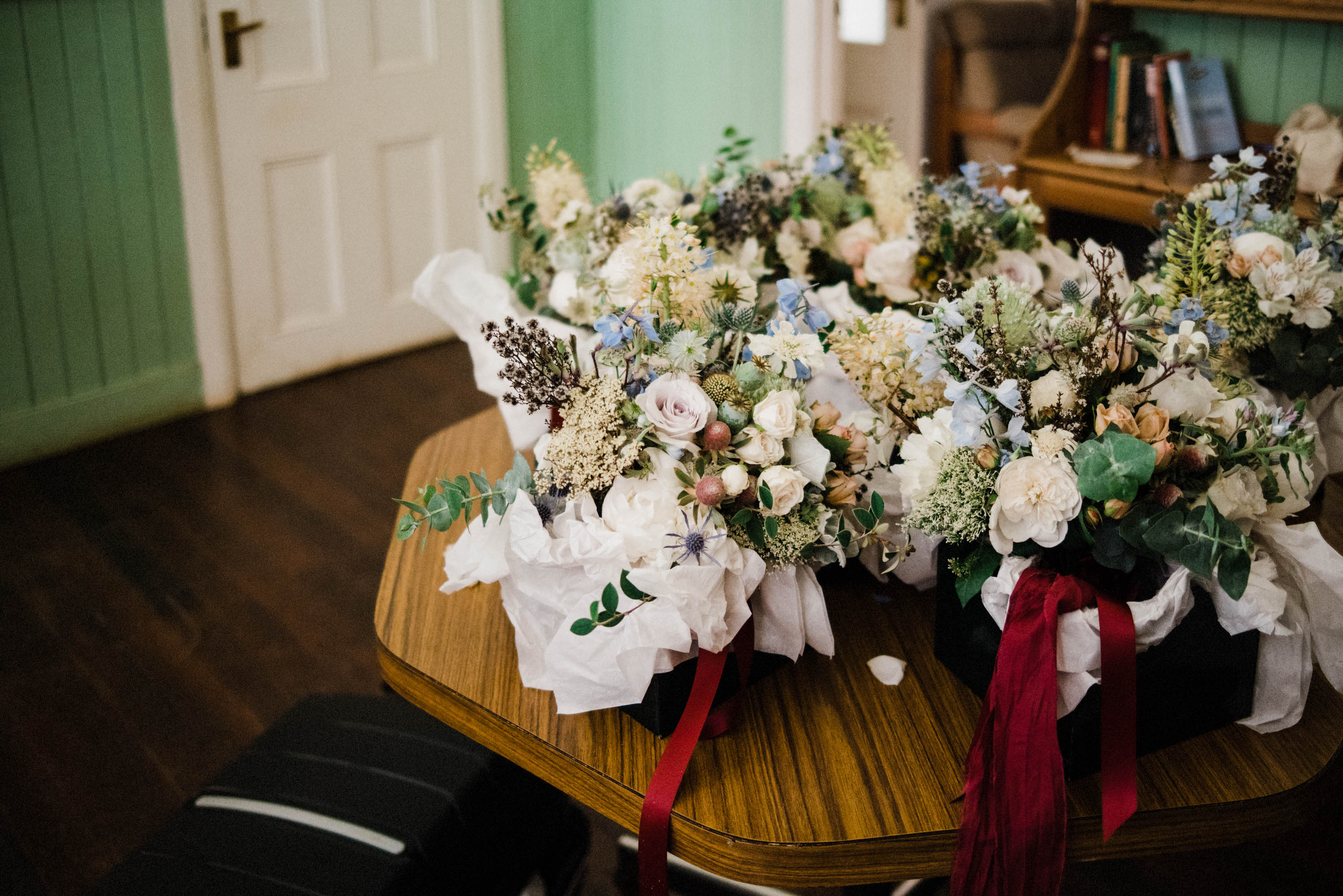 A photo of the bride's bouquet together with bridesmaids' bouquets by Covet Collect at a Donnelly River Village wedding.
