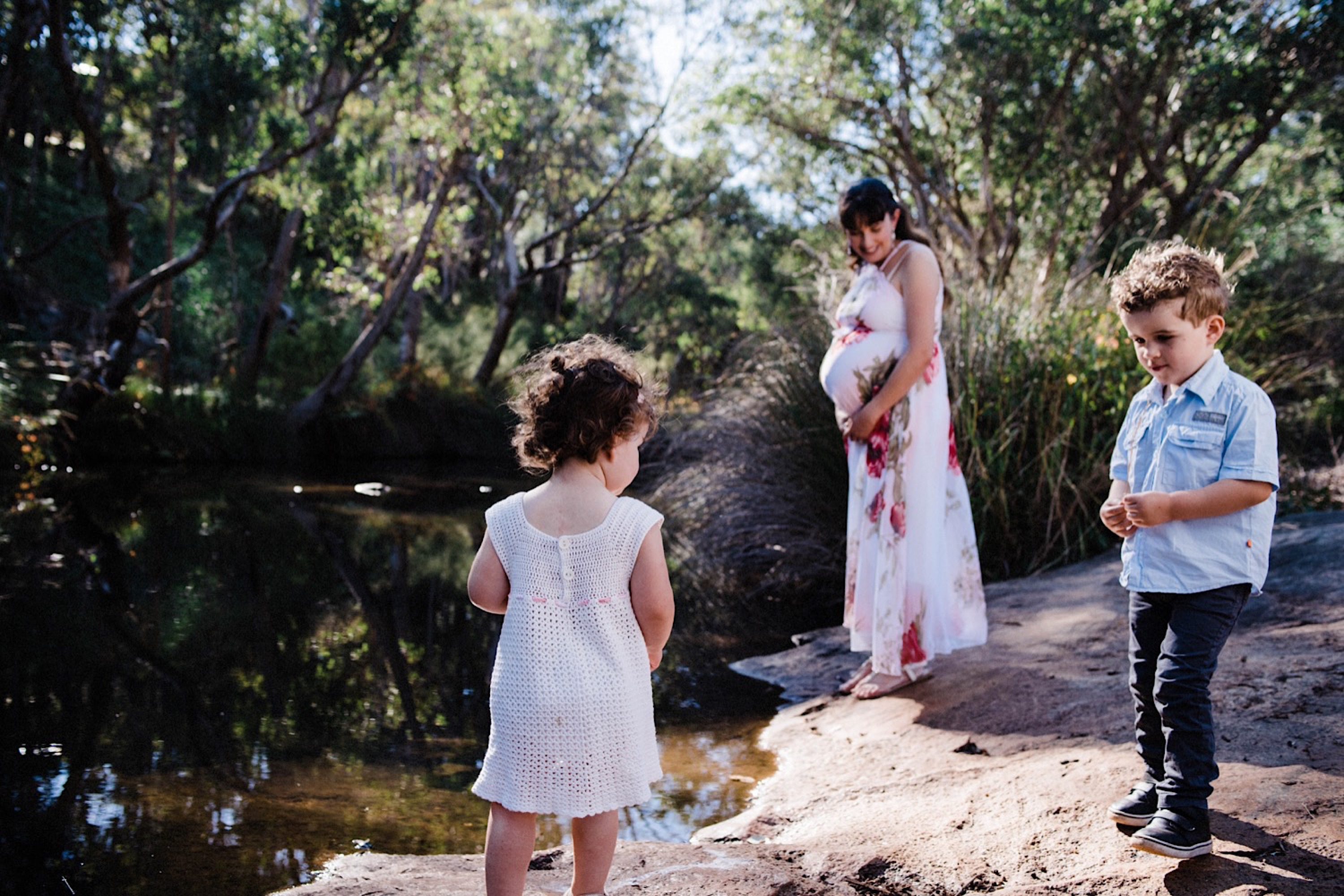 An authentic family photo of two young children standing by a creek with their Mum in the background.
