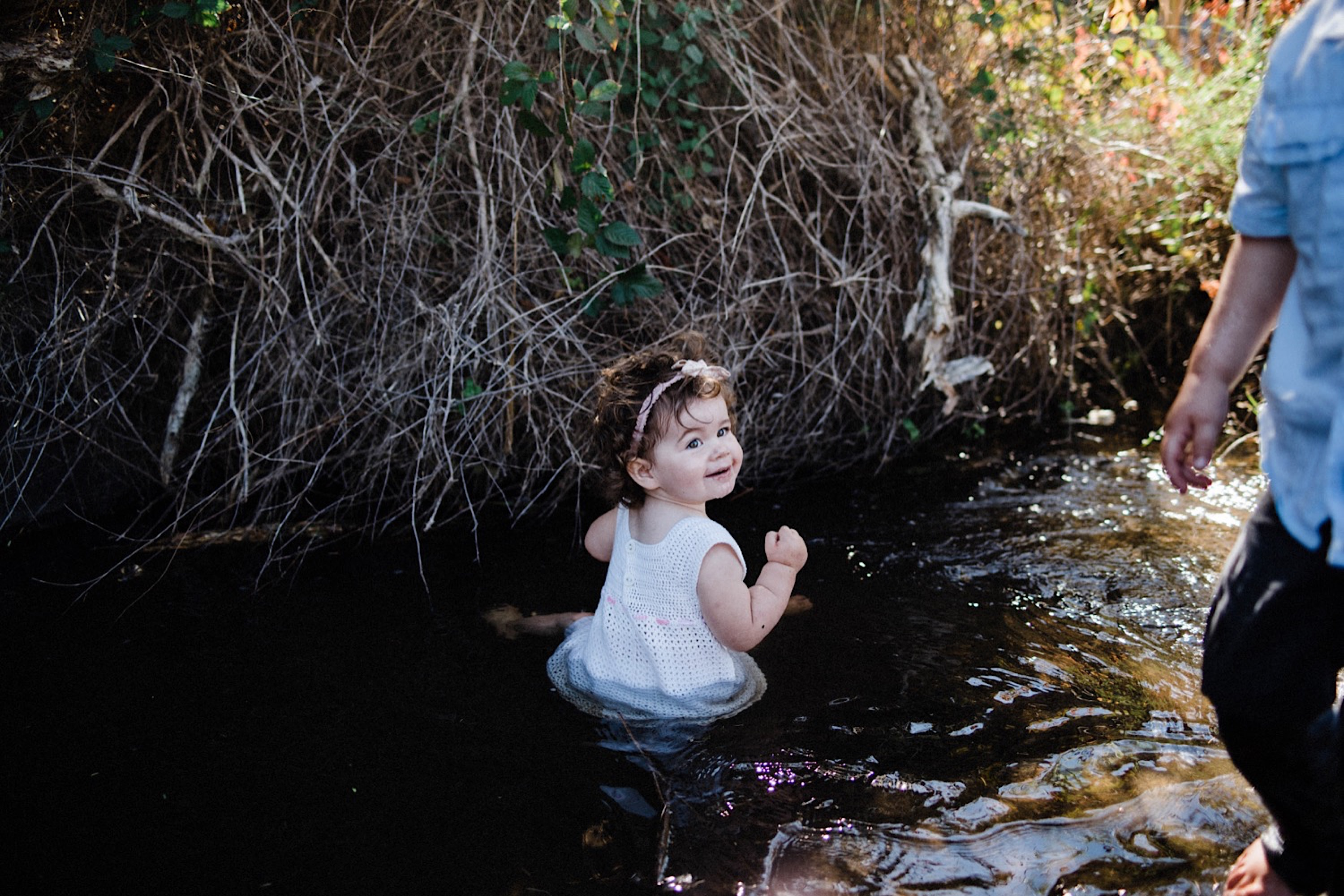 A family photo of a toddler sitting happily in a creek at the end of their Wild Lifestyle Family Portrait Photos.
