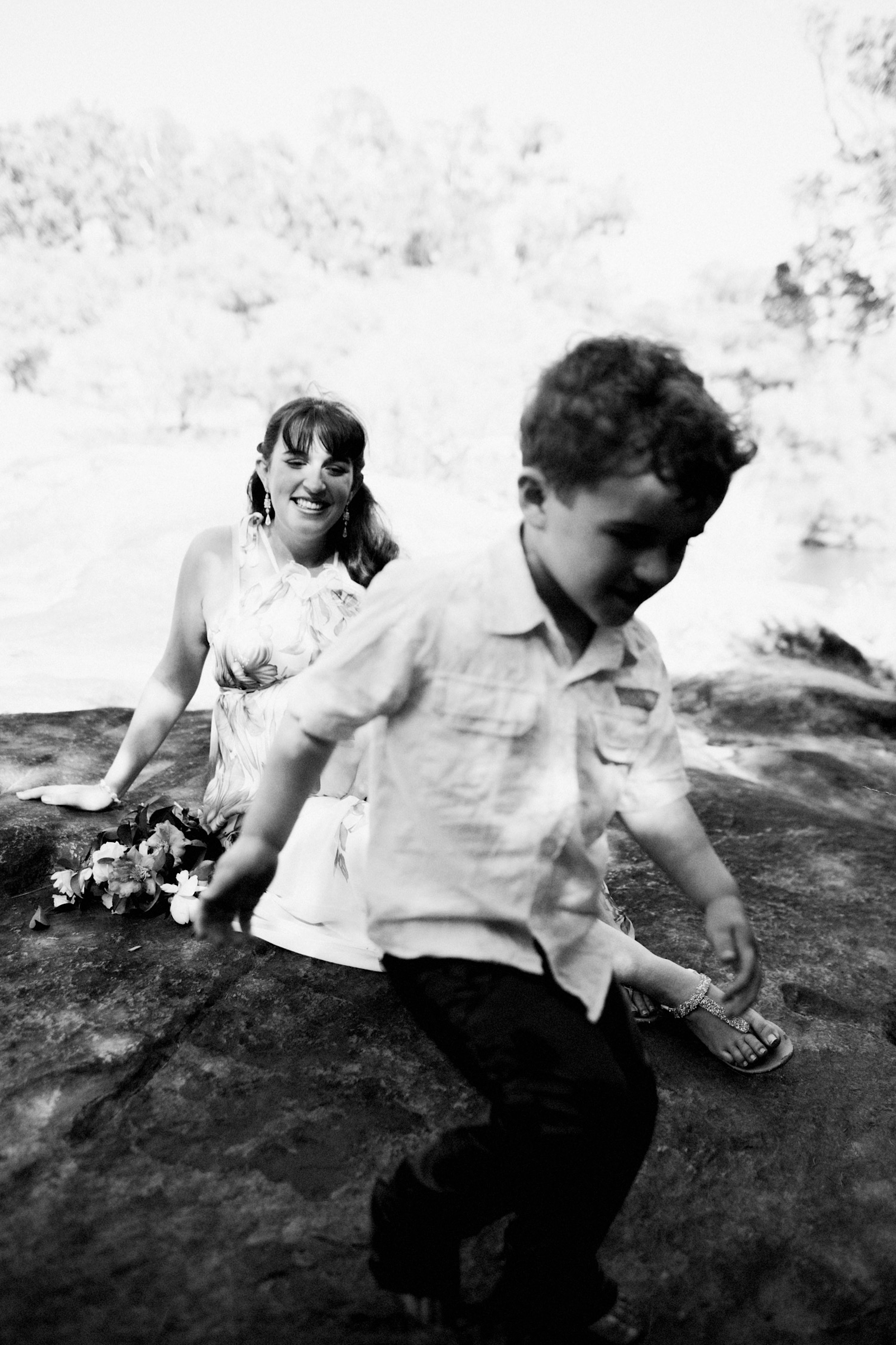 A candid image of a little boy running in front of his Mum during some Lifestyle Family Photographs as the Mum laughs.
