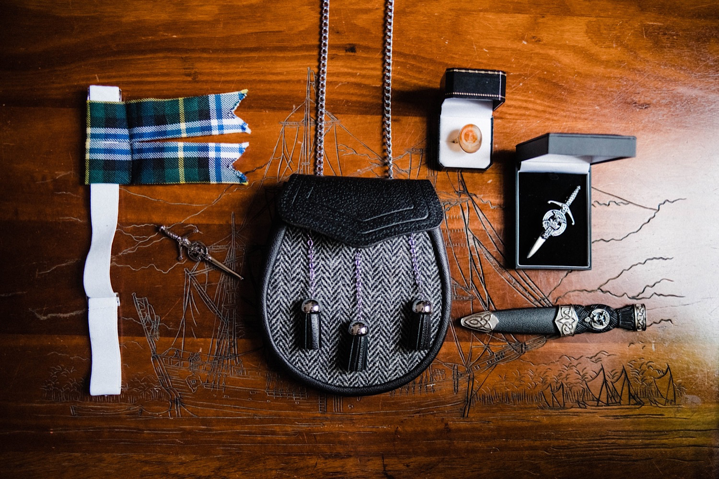 A flatlay on an engraved wooden table of the groom's wedding details, including tartan for his socks, his sporran, a ring, a sword pin and a small dagger.