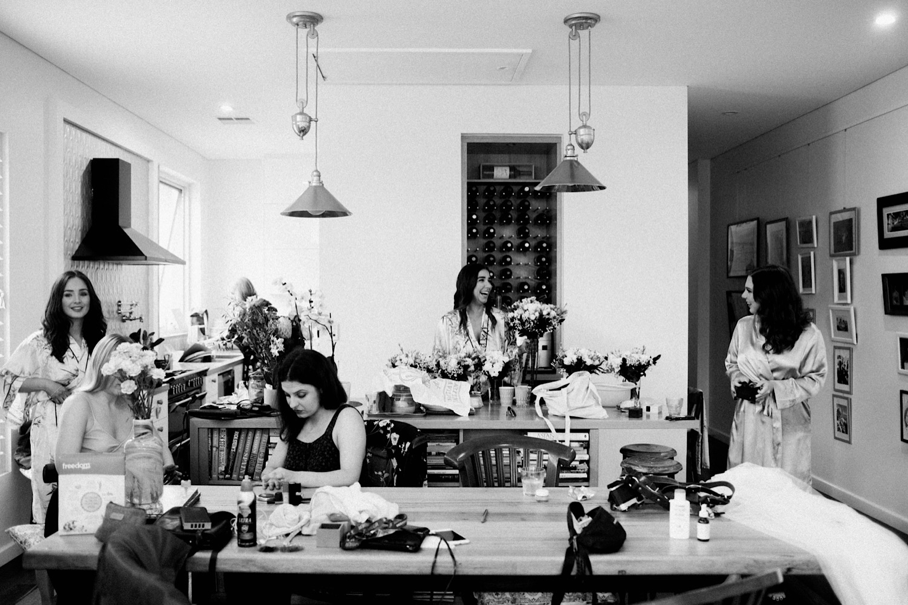 A black & white candid wedding photo of the bride & her bridesmaid's getting ready in the kitchen in the morning.