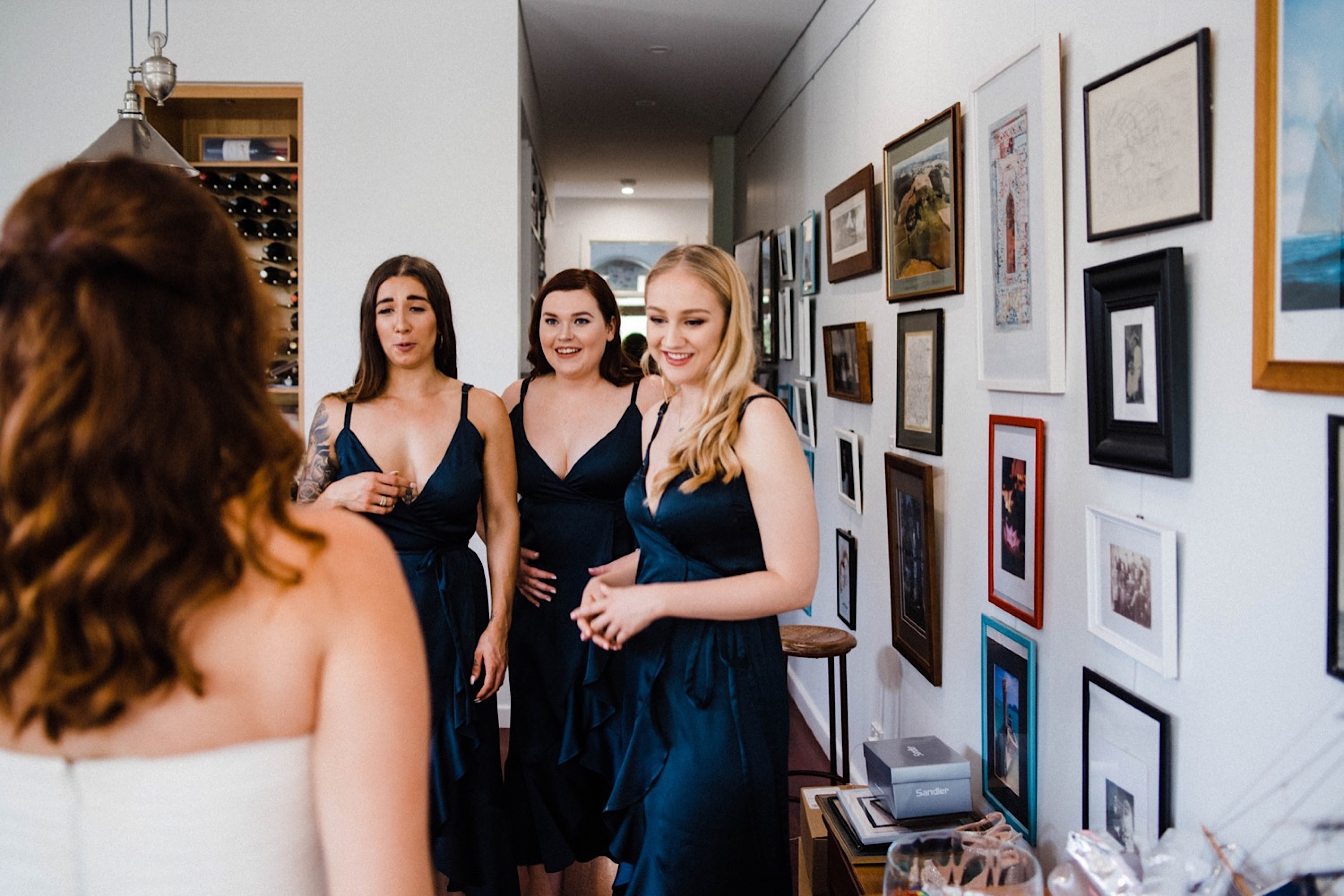Documentary Wedding Photography of the bridesmaid's, who are wearing blue, reacting to seeing the bride in her dress for the first time.