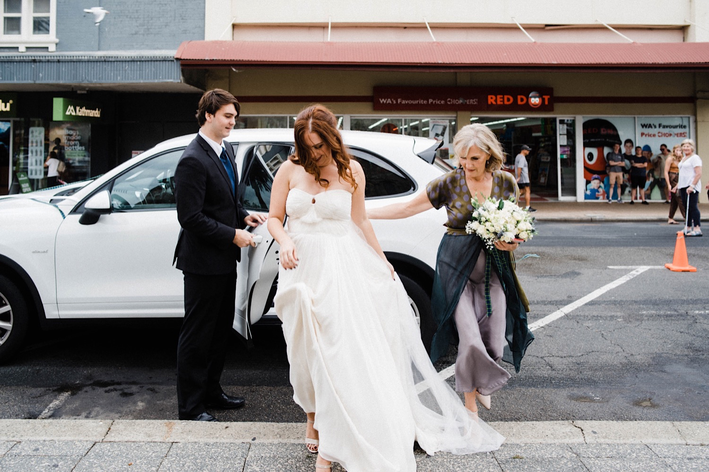 A candid wedding photo of the bride stepping out of the car, after arriving at the ceremony, with the help of her Mum and brother.