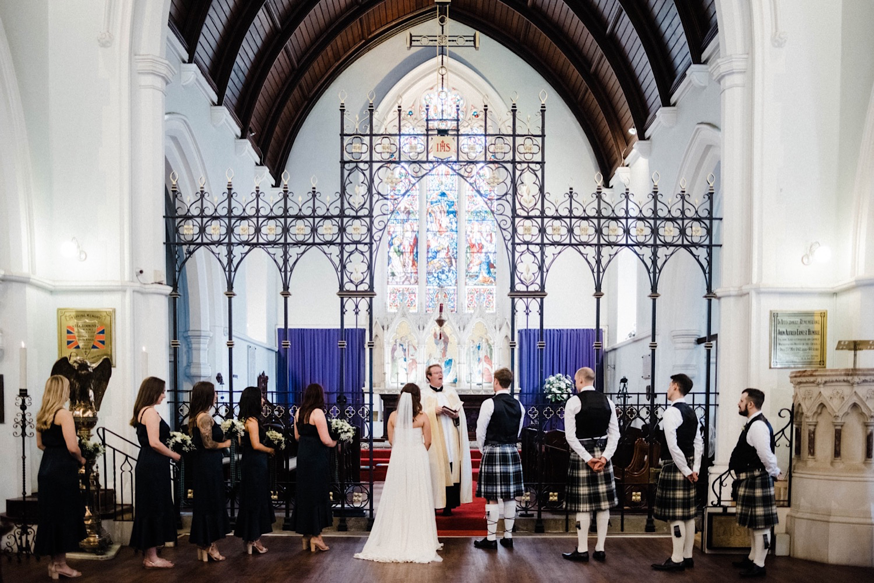 A wide shot of the wedding party and bride & groom standing at the front of St John's Anglican Church at the beginning of the wedding ceremony.