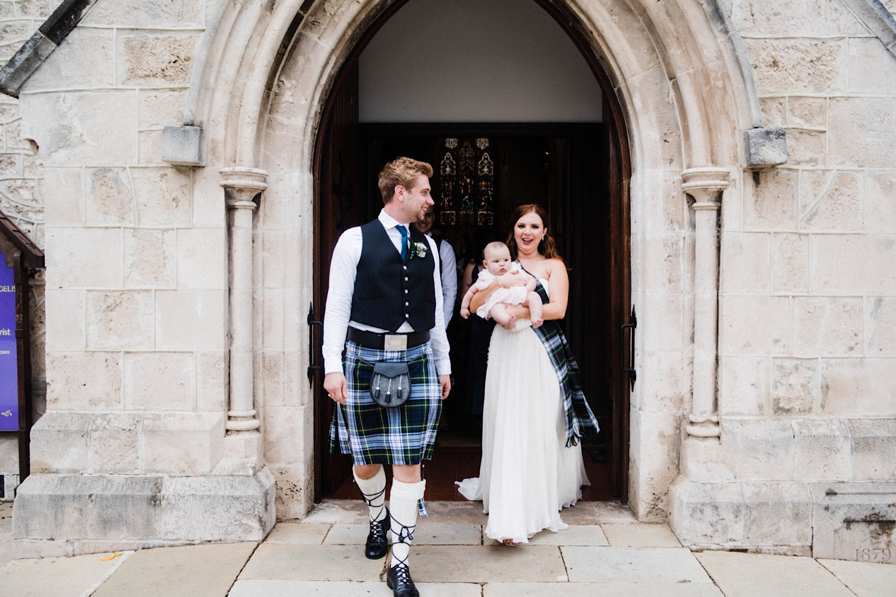 A candid portrait of the bride & groom walking out of St John's Anglican Church at the end of the wedding, as their bride hold's a friend's baby.