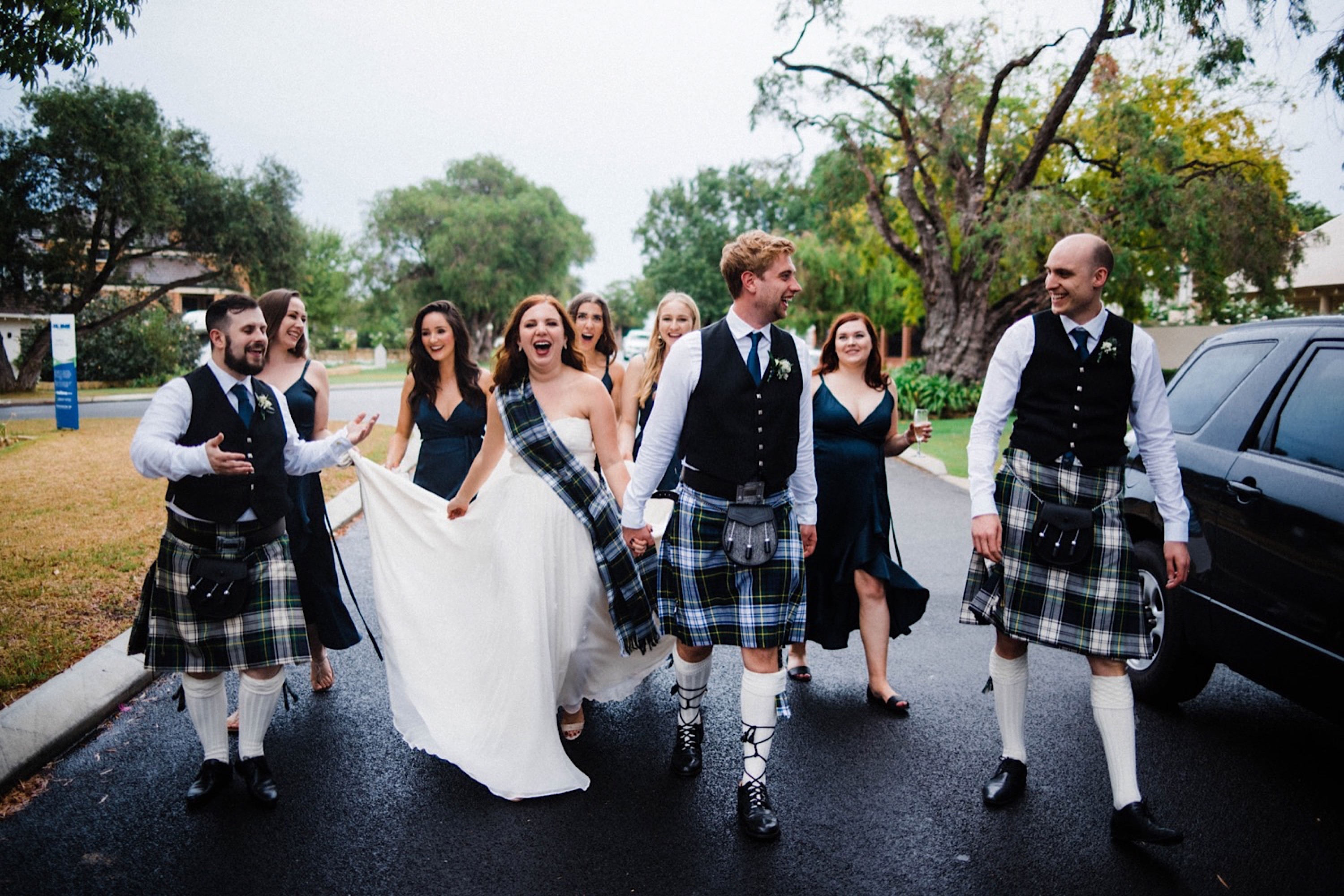 A documentary wedding portrait of the bride and her bridesmaids, the groom and his groomsmen who are wearing kilts, walking down a suburban street in the rain.