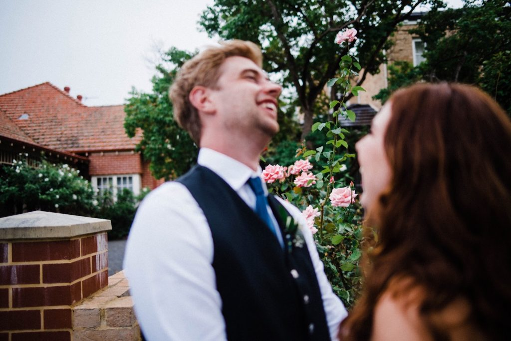 A candid wedding portriat of the groom leaning back and laughing in front of a rose garden.