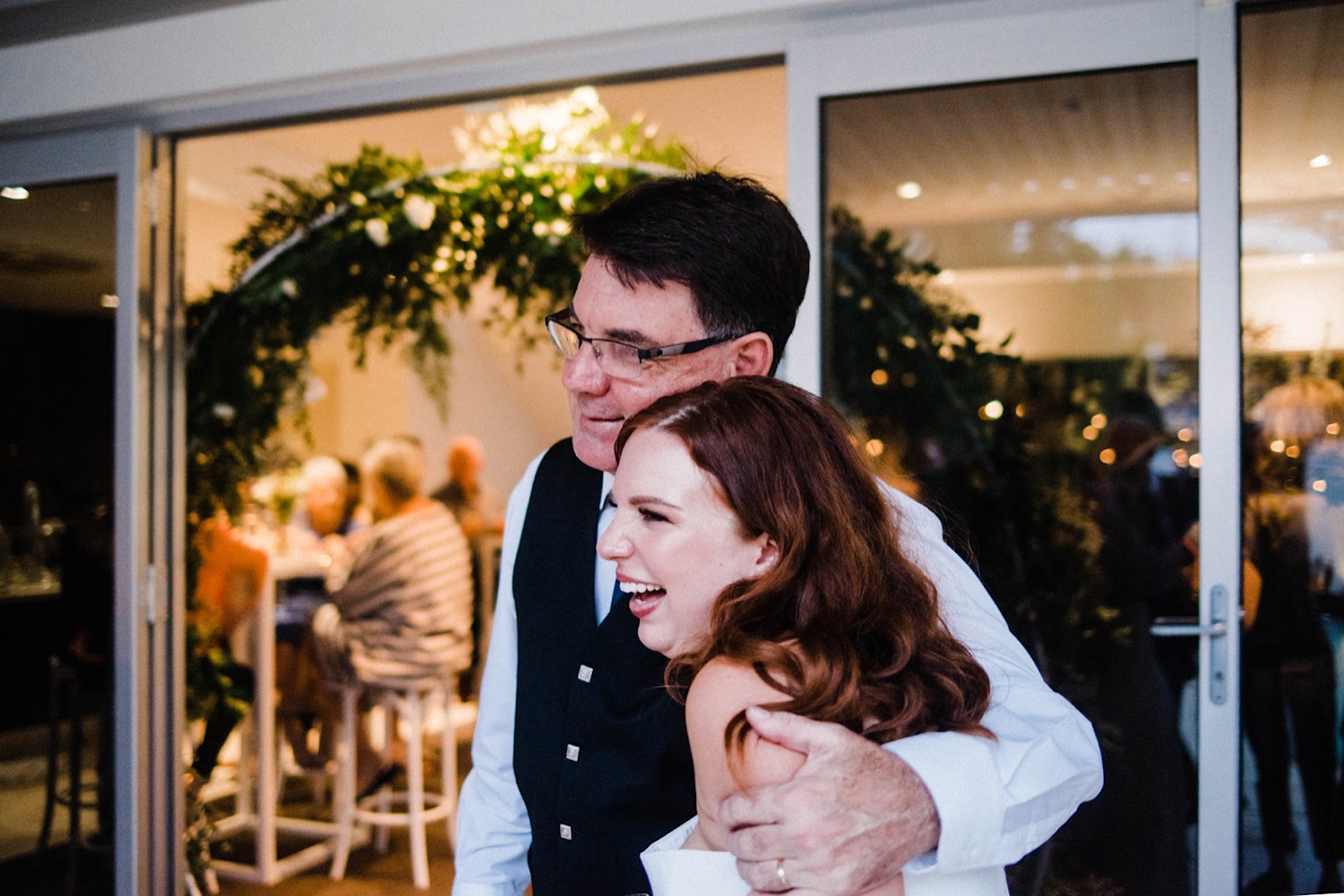 Documentary wedding photography of the bride hugging her Dad at her Sustainable Backyard Wedding.