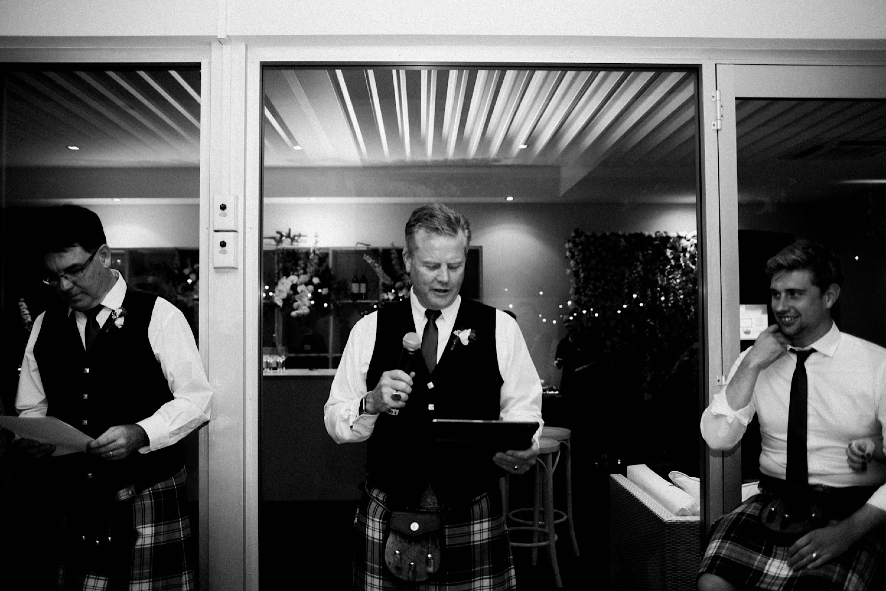 A black & white documentary photo of the father's of the bride & groom during speeches.