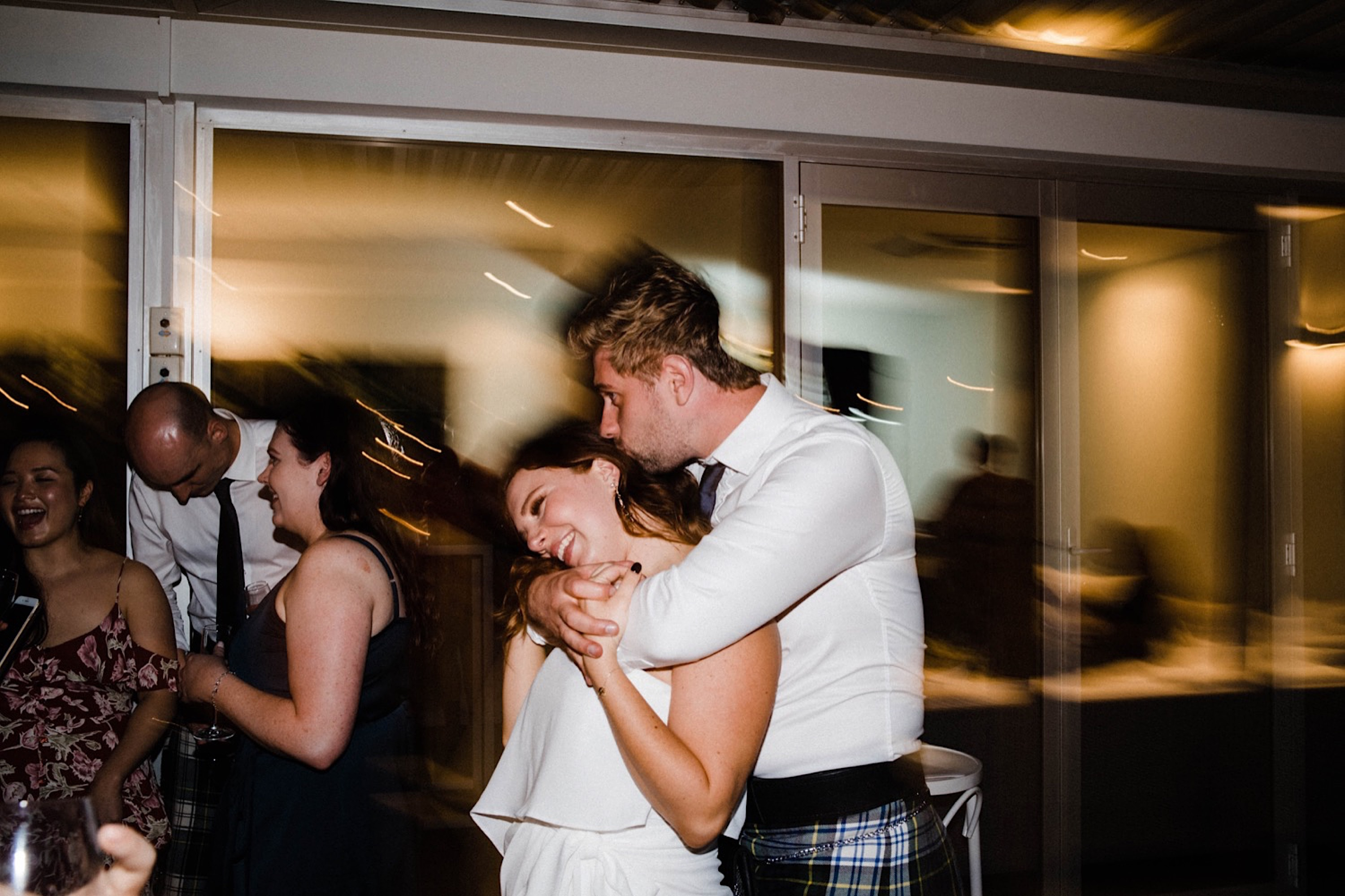 A wedding photo of a bride & groom dancing together at their Sustainable Backyard Wedding.