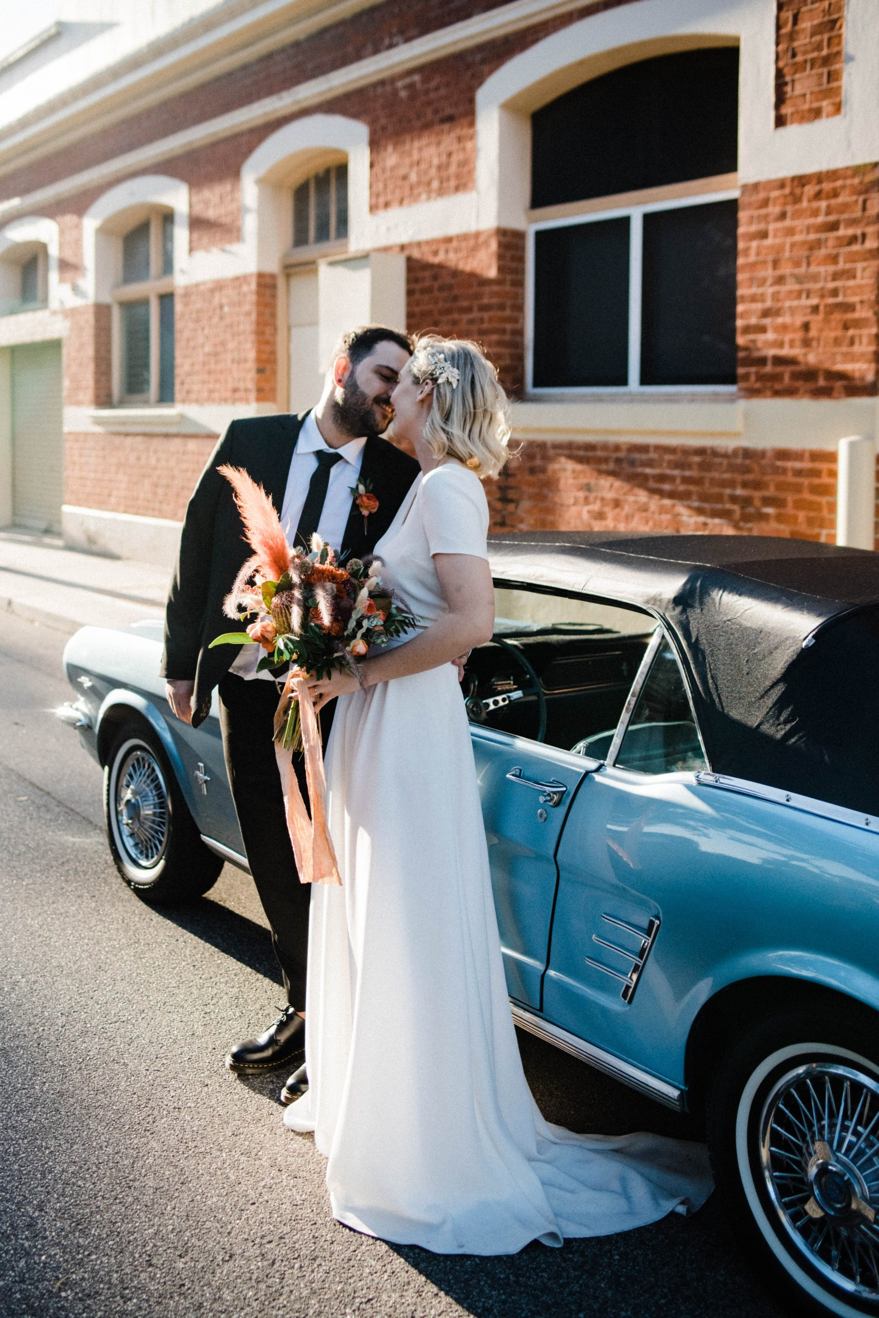 A photo of a newly married couple, standing in front of a vintage blue, convertible mustang in front of Fridays Studio