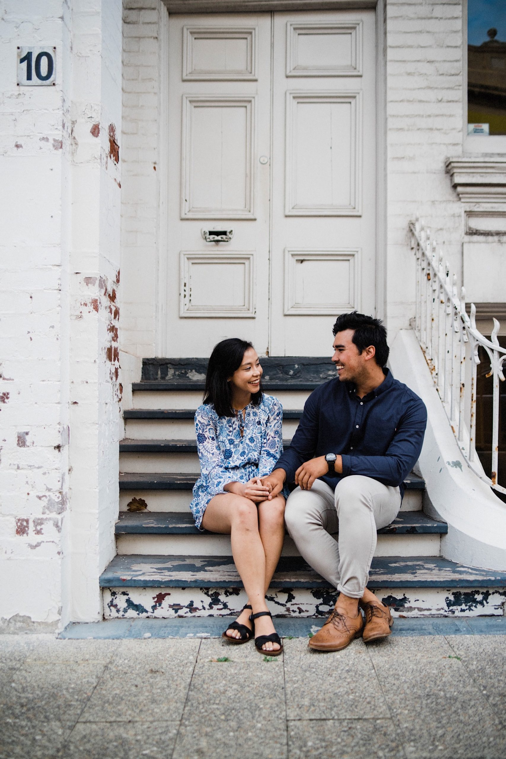 An engagement portrait of a couple sitting on some stairs in front of a heritage building in Fremantle