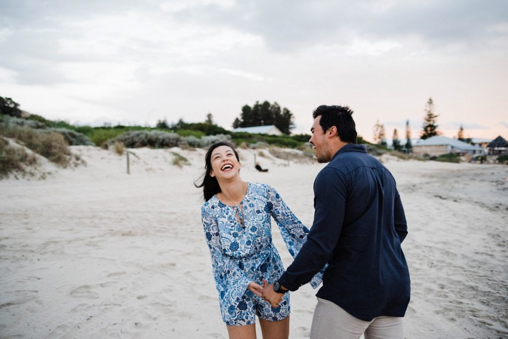 A Fremantle engagement photo taken at Bathers Beach of a couple laughing loudly and holding hands.