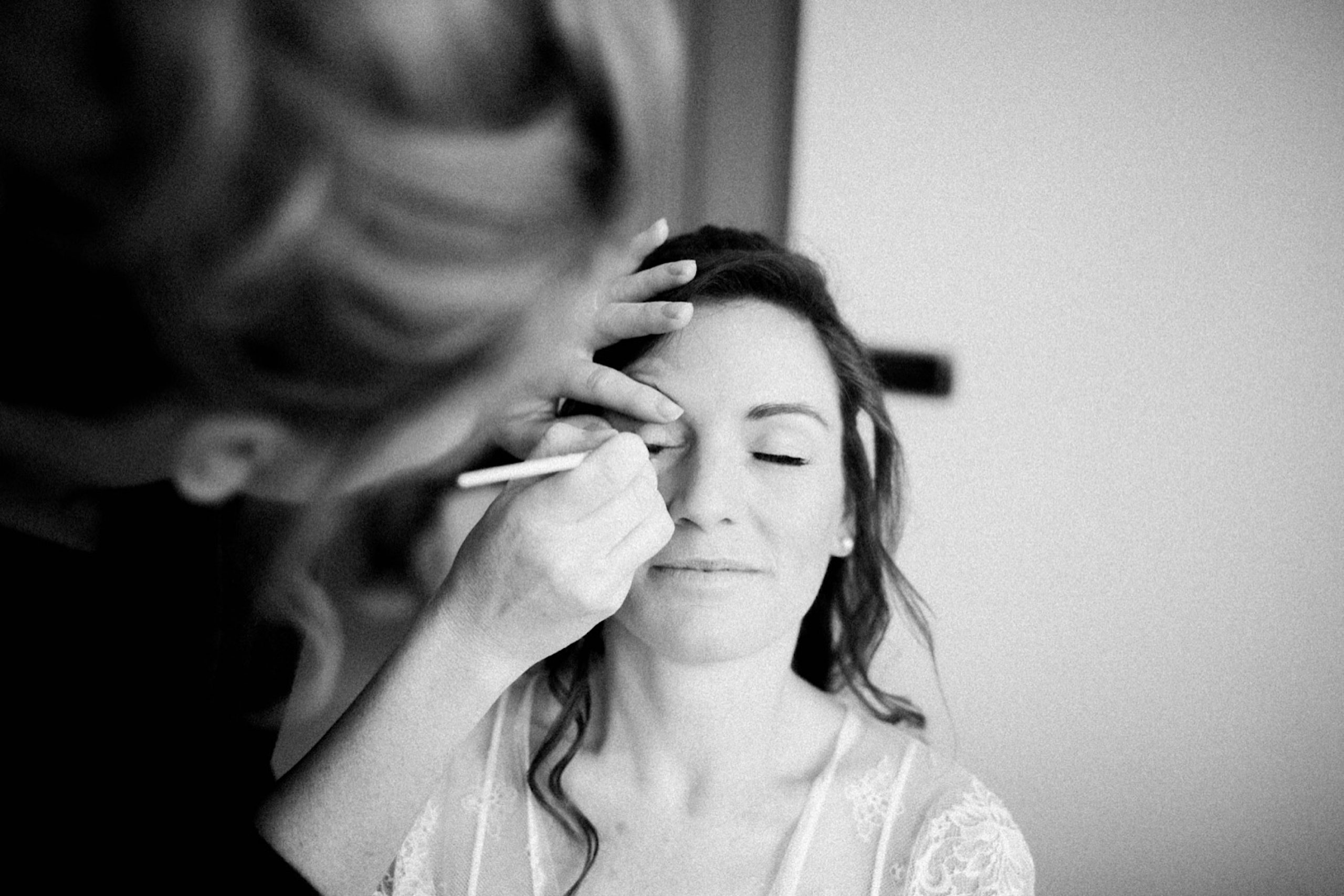 Black and white Destination Wedding Photography of a bride having her makeup done.
