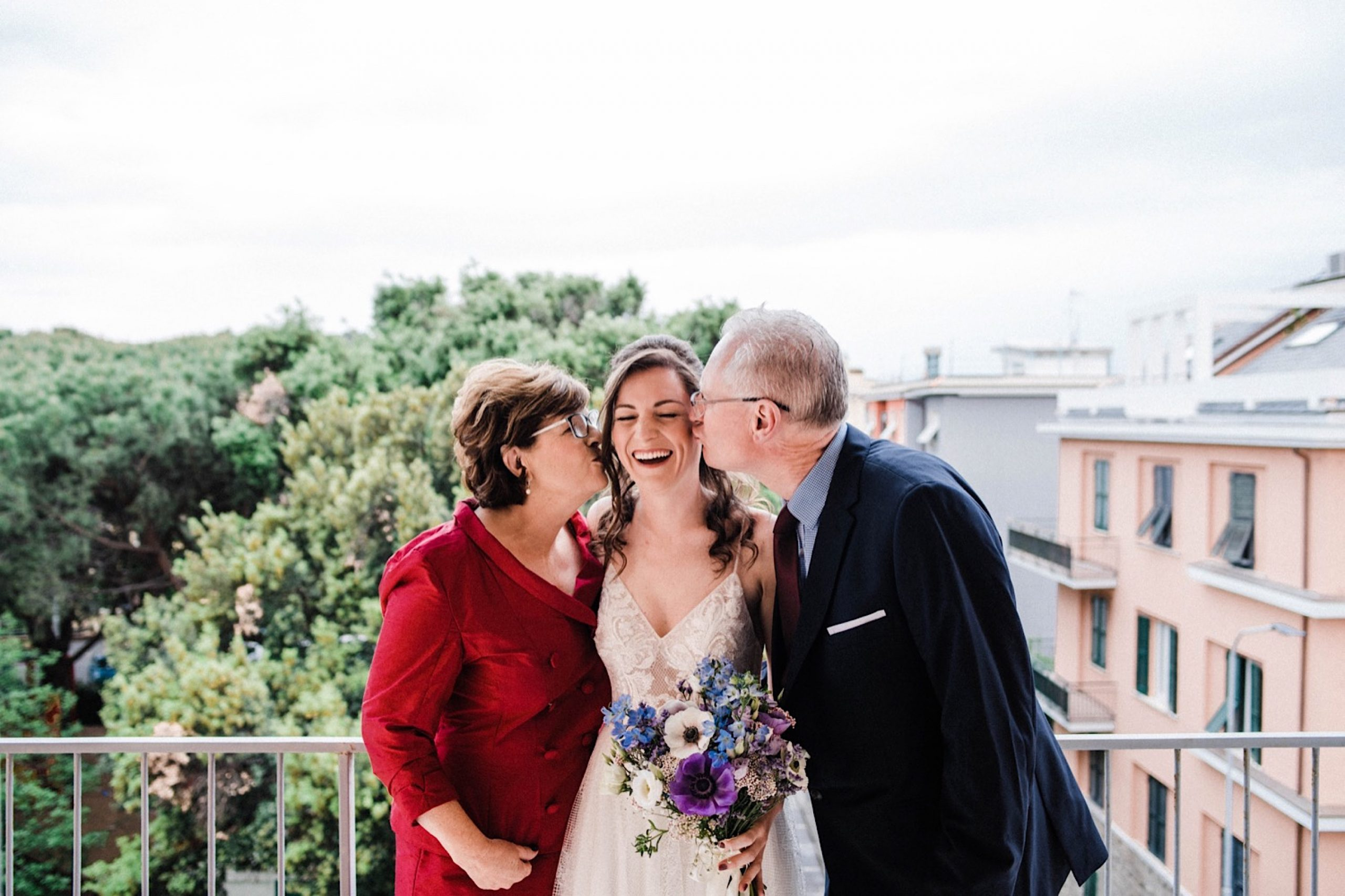 A wedding photo of the bride with her parents, who are kissing her on the cheek, on a balcony in Sestri Levante on the Italian Riviera.