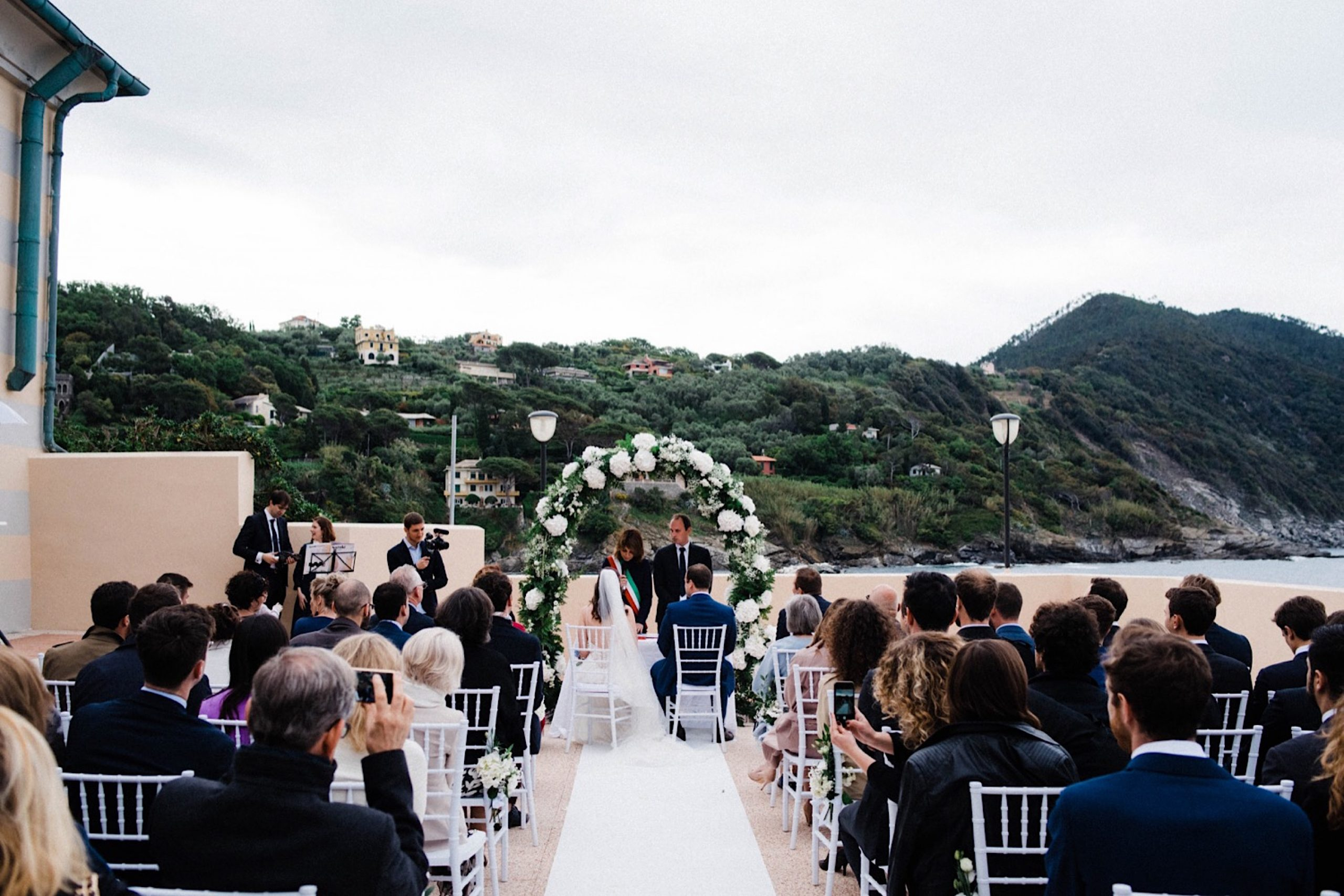 A photo of a Wedding Ceremony at the ex-Convento dell'Annunziata with the groom & bride sitting in front of a floral arch.