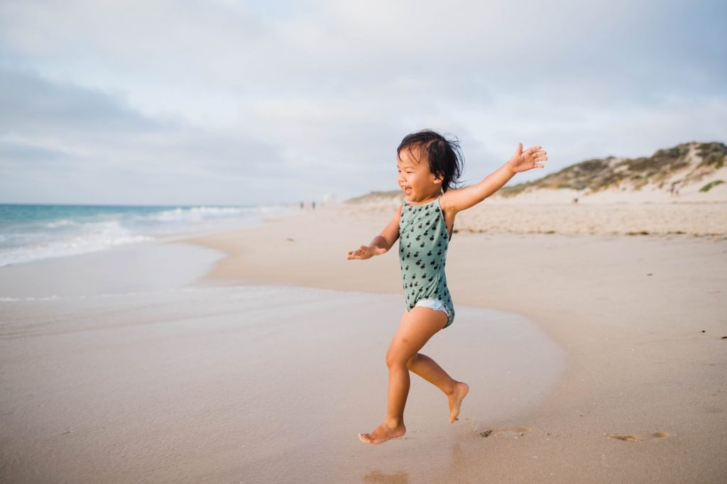 A child leaps through the air running towards the ocean at Floreat Beach.