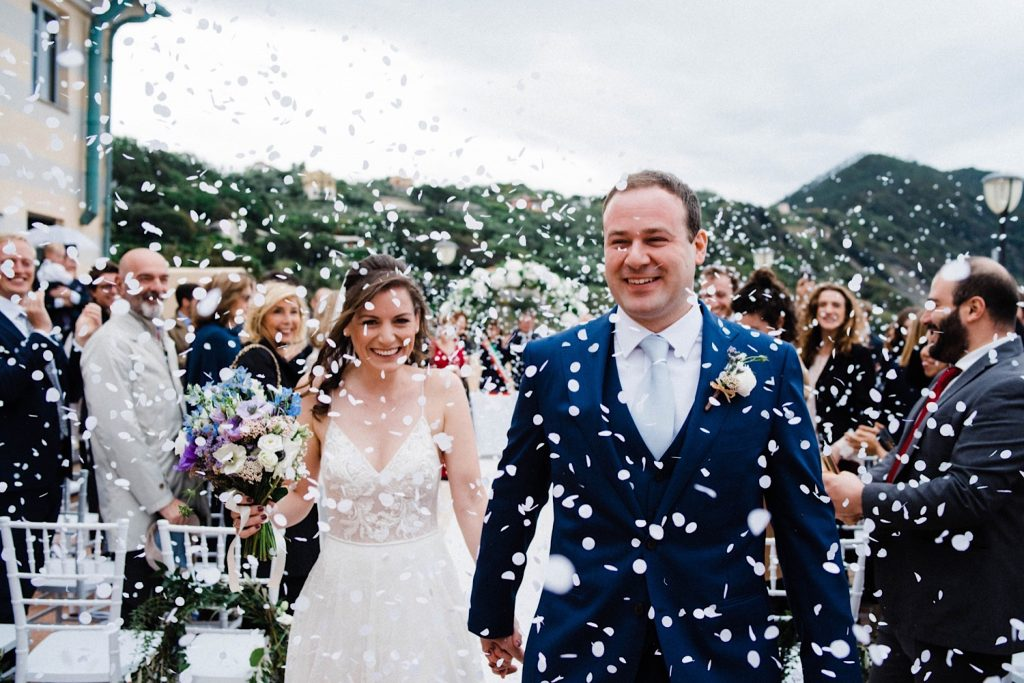 Italian Riviera Destination Wedding Photography of the bride & groom walking back down the aisle as guests throw confetti all around them.