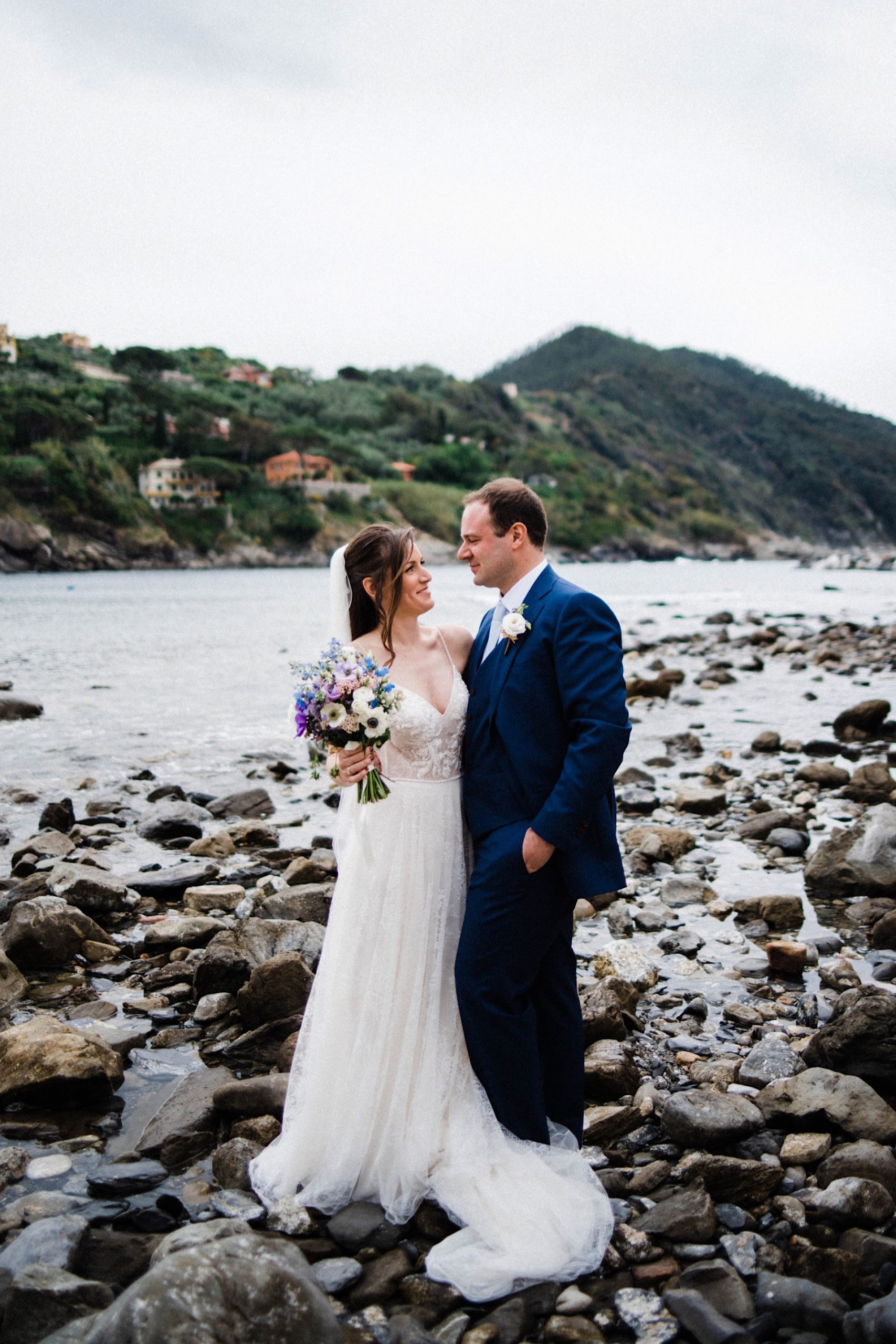 Sestri Levante Destination Wedding Photography of a bride and groom standing together in front of the Bay of Silence.